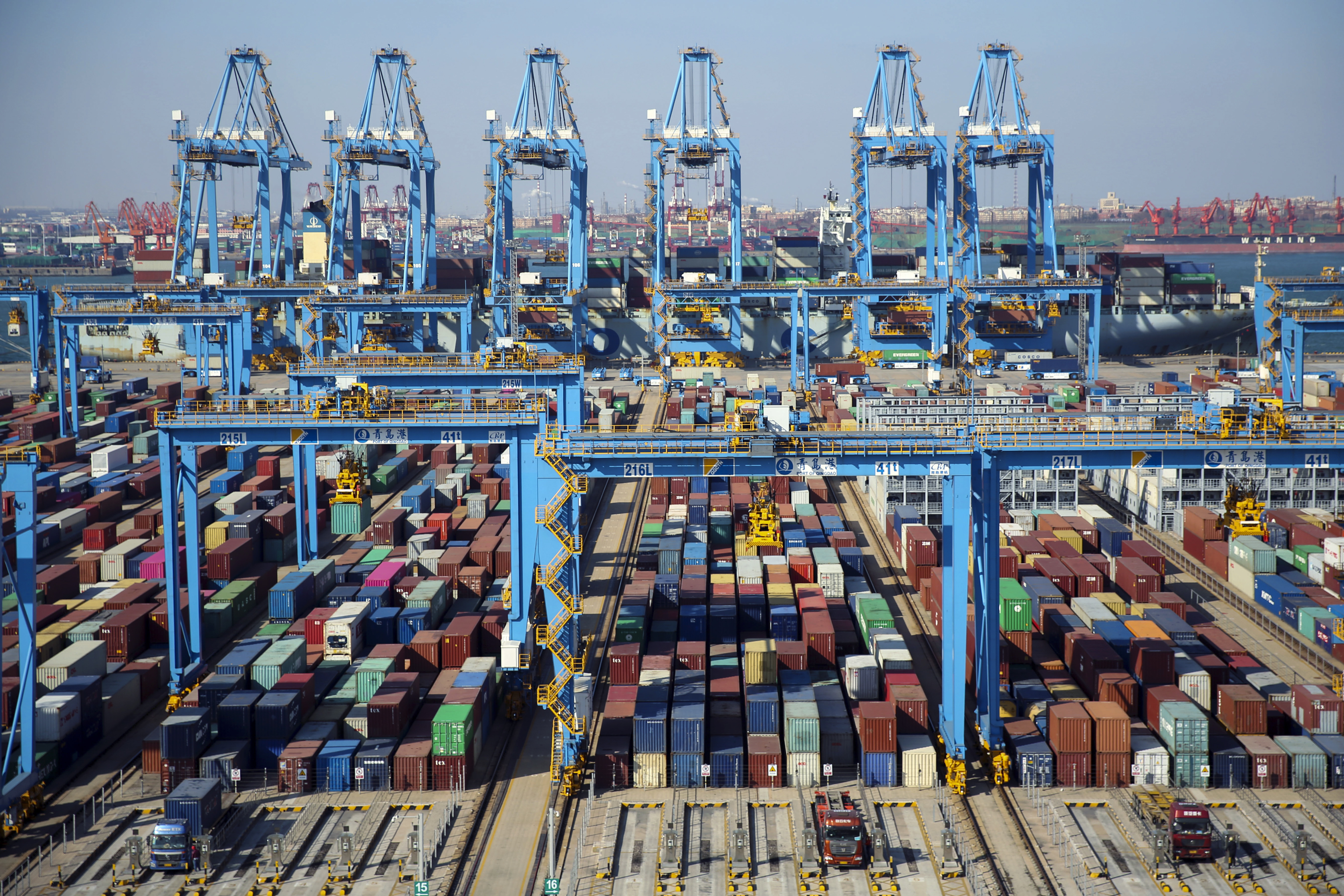 Trucks load containers at the automated container dockyard in Qingdao in east China's Shandong province on Nov. 28, 2019.