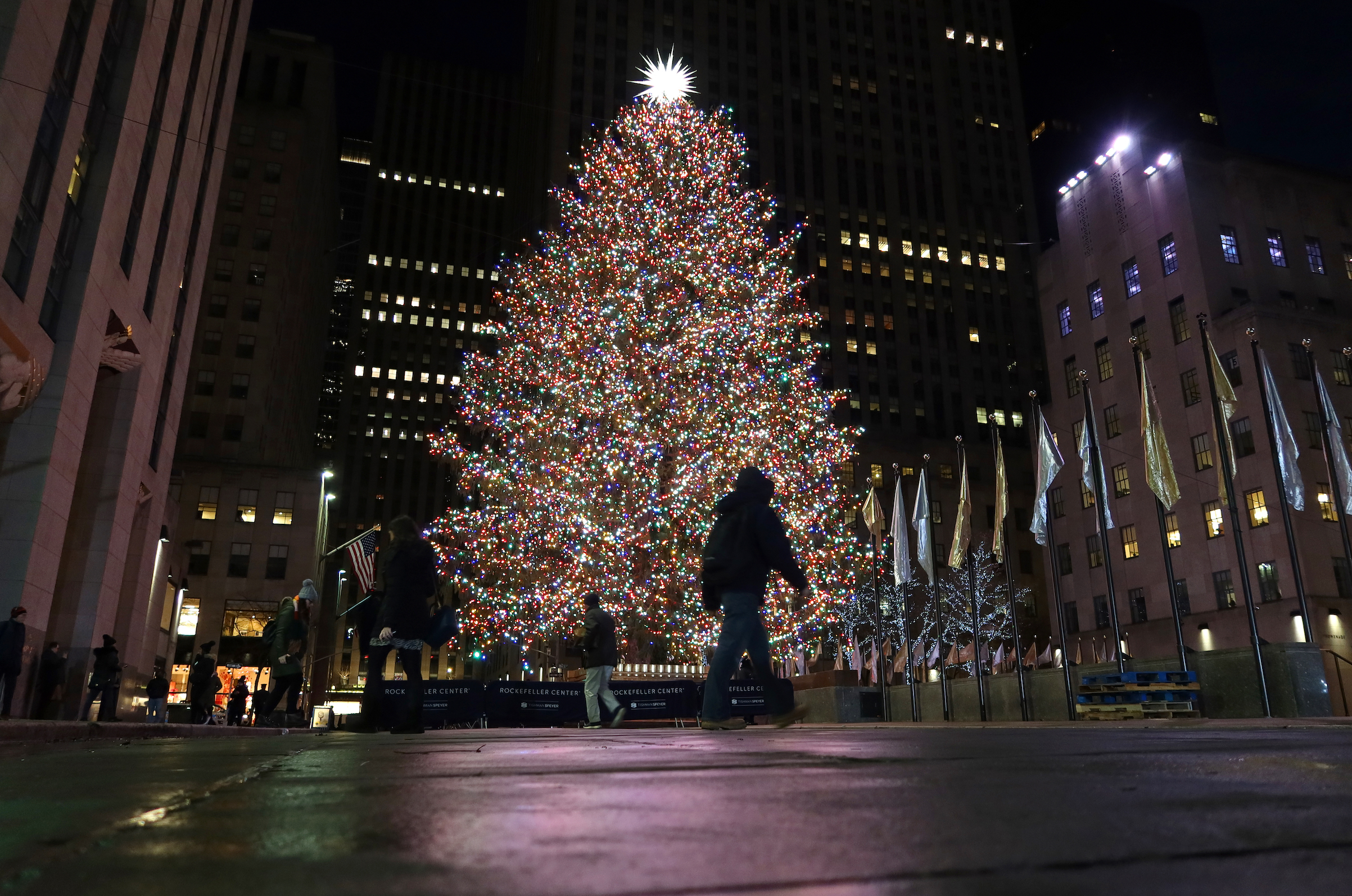 A man walks past the Christmas tree in Rockefeller Center before sunrise on Dec. 5, 2019, in New York City.