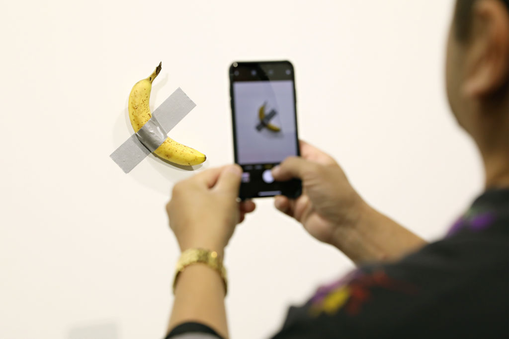 A person takes a photograph of Maurizio Cattelan's  Comedian  at Art Basel in Miami on Dec. 6, 2019.