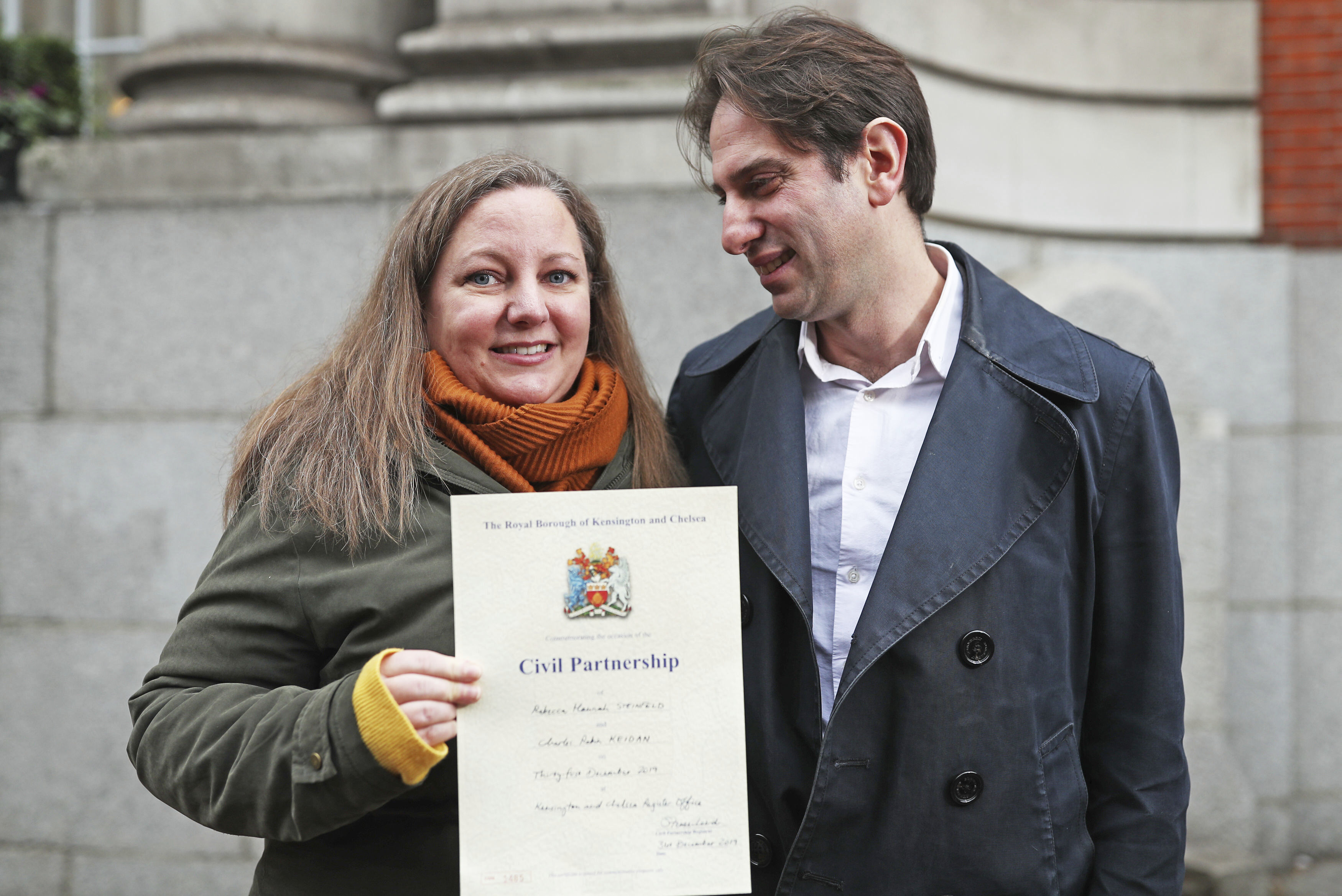 Rebecca Steinfeld and Charles Keidan pose for the media outside at Kensington and Chelsea Register Office after registering for a civil partnership, in London on Dec. 31, 2019.