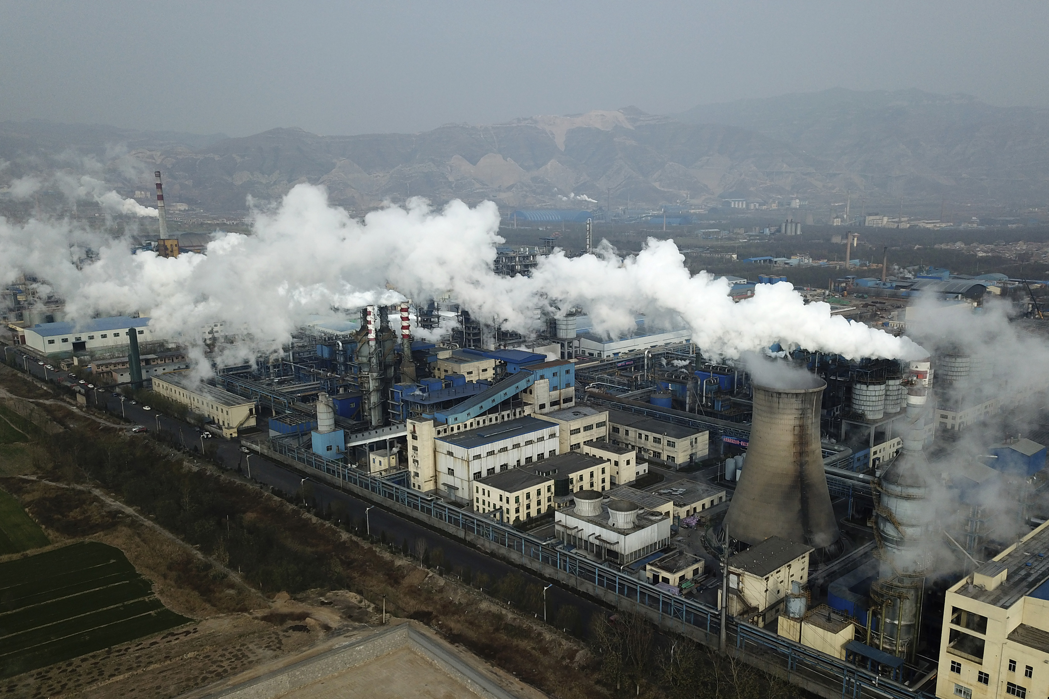 Smoke and steam rise from a coal processing plant that produces carbon black, an ingredient in steel manufacturing, in Hejin in central China's Shanxi Province on Nov. 28, 2019.