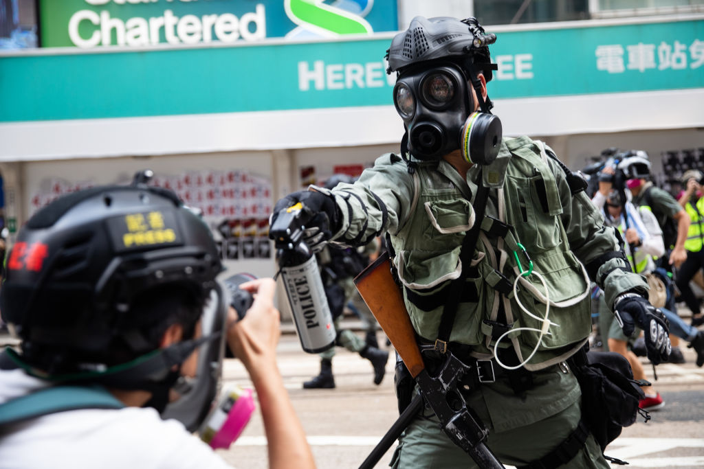 A riot police officer aims pepper spray at a journalist during a protest in Hong Kong on Sept. 29, 2019.