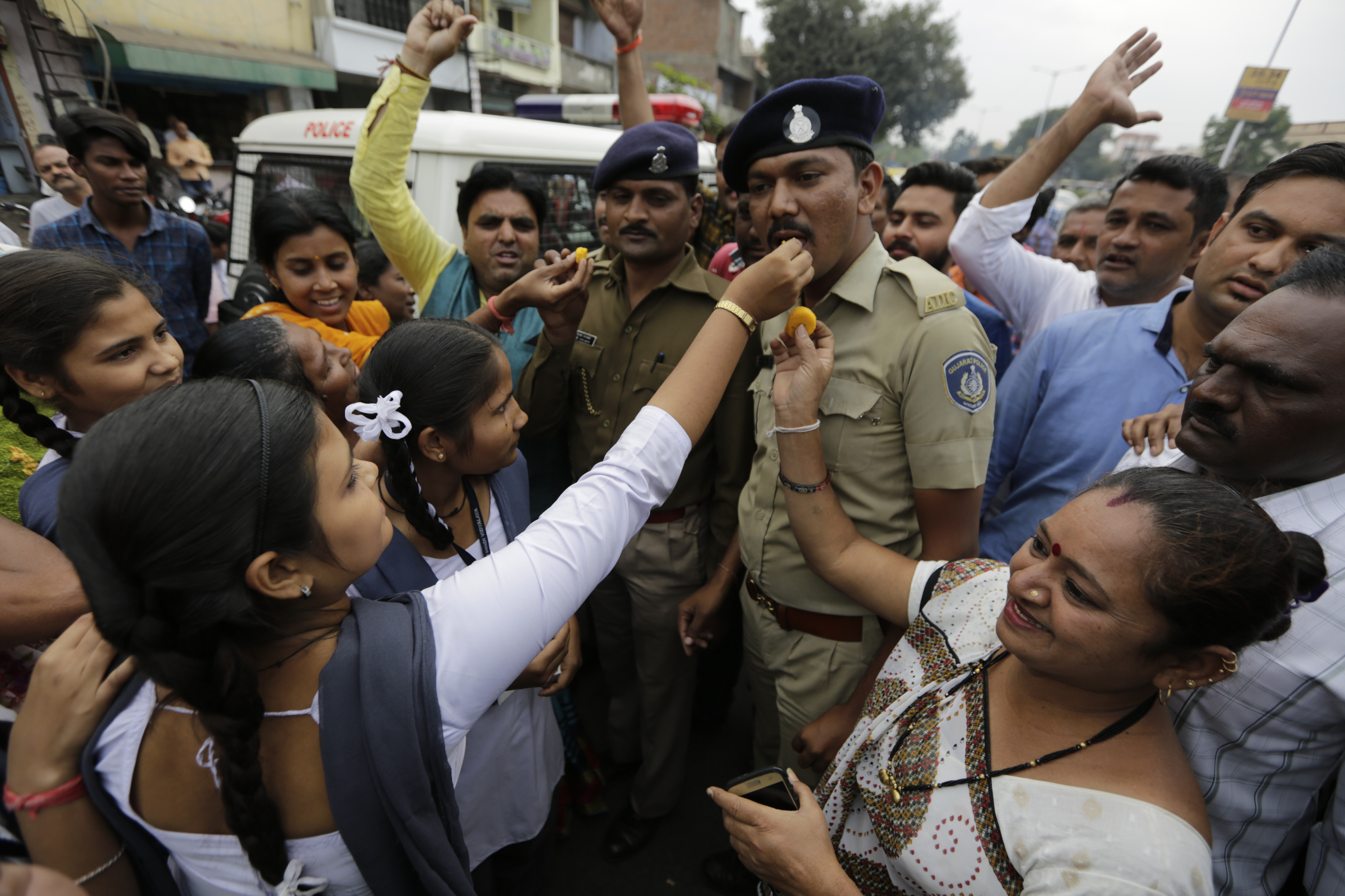 Indian feed sweets to policemen on duty and shout slogans in favor of police to celebrate killing of four men suspected of raping and killing a woman in Shadnagar in southern state of Telangana, in Ahmadabad, India, Friday, Dec. 6, 2019. Police on Friday fatally shot four men suspected of raping and killing a woman in southern India, drawing both praise and condemnations in a case that has sparked protests across the country.