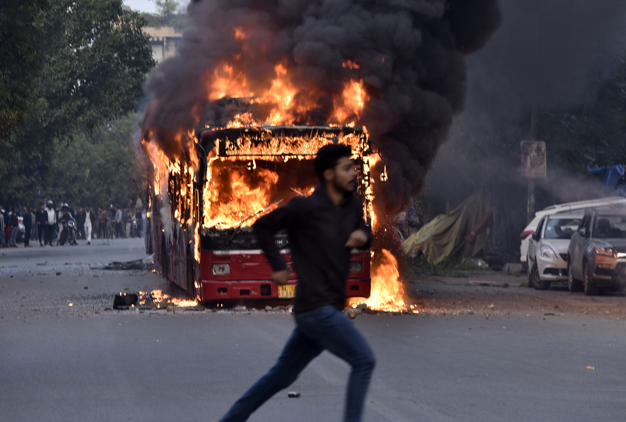A burning bus is seen after it was set on fire by demonstrators during a protest against the Citizenship amendment Act (CAA) at New Friends Colony in New Delhi, India on Dec. 15, 2019.