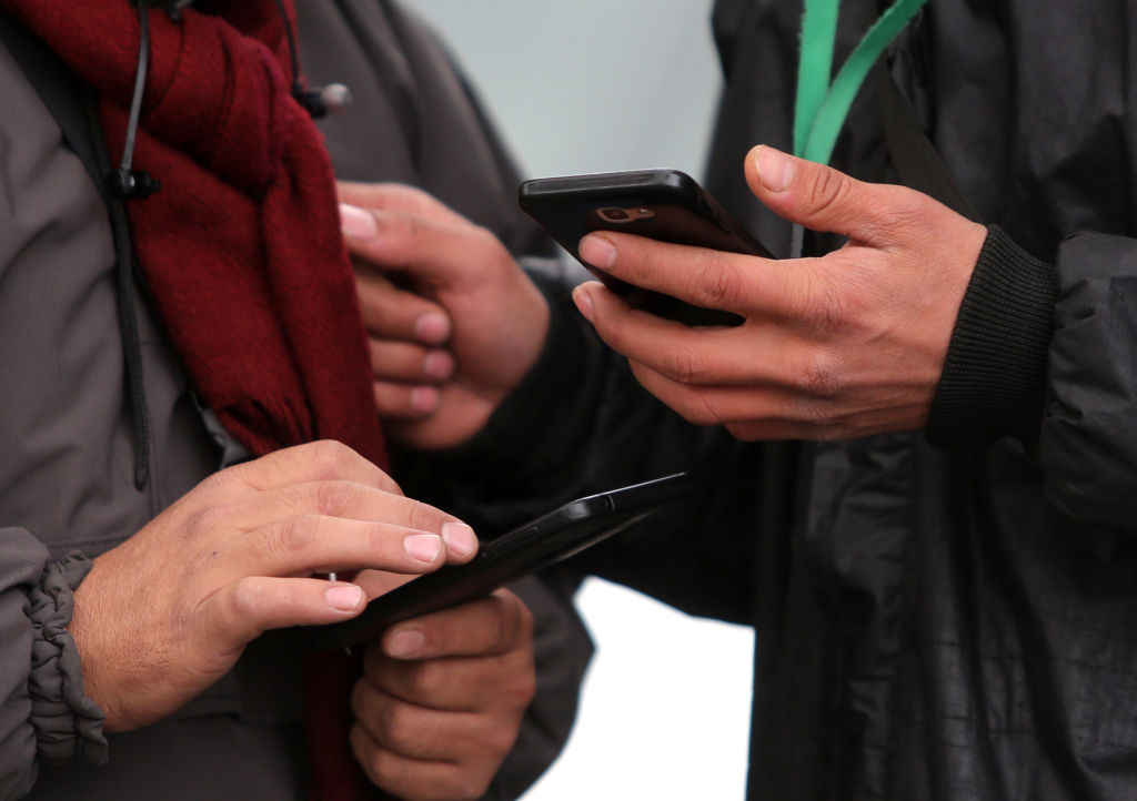 People hold smartphones while walking in the Iranian capital Tehran on Nov. 23, 2019.