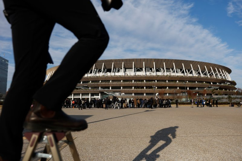 A photographer stands on a step stool to photograph the new National Stadium on Dec. 15, 2019, in Tokyo.