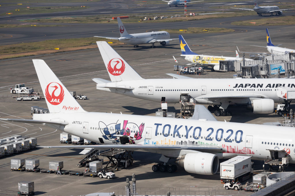 Japan Airlines (JAL) airplanes displaying Tokyo 2020 Olympic graphics are parked at the gates of Tokyo's Haneda Airport on Nov. 7, 2019.