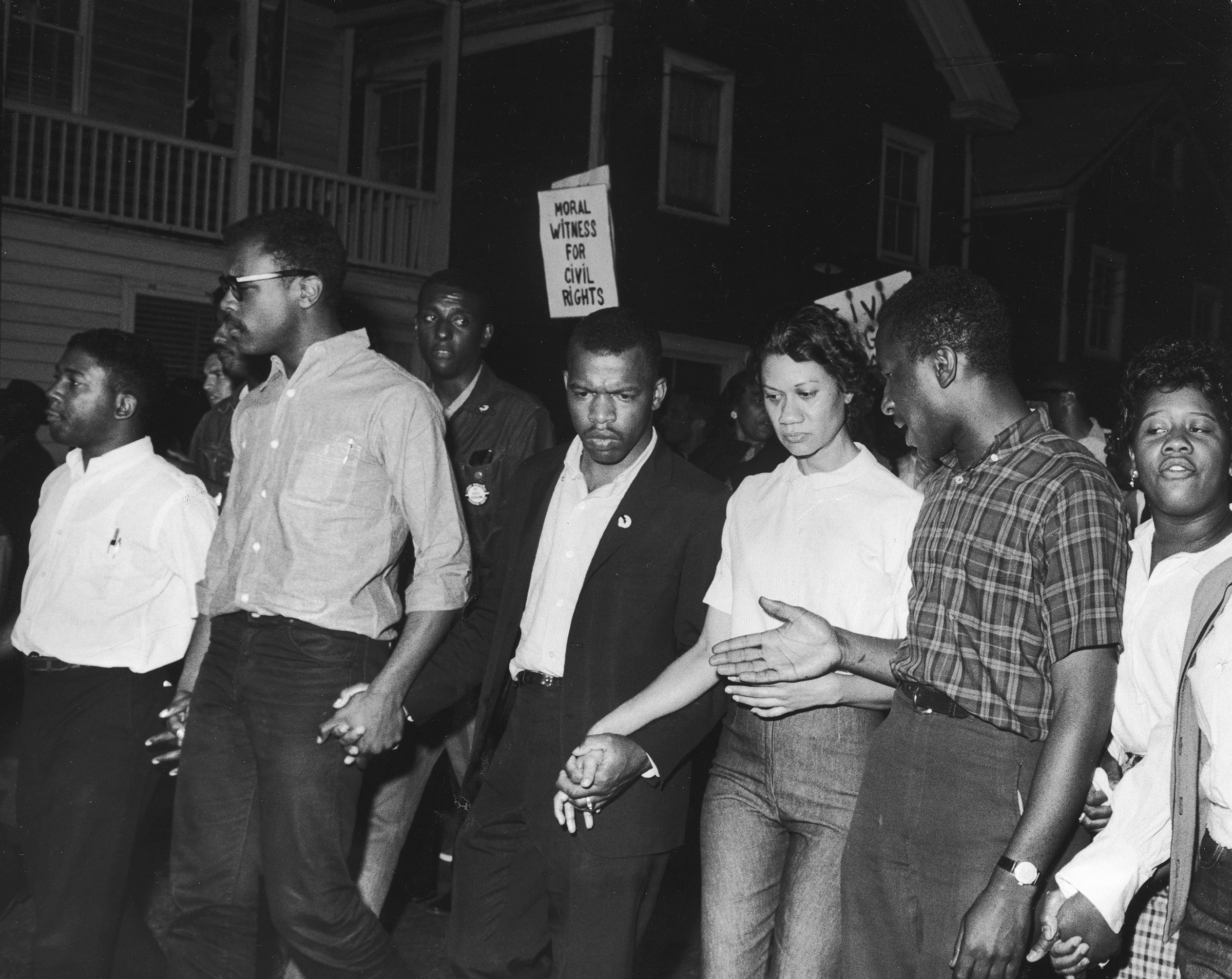 Civil Rights leaders, including future Congressman John Lewis (third left) and Gloria Richardson (third right), chair of the Cambridge Non-Violent Action Committee, link hands as they march in protest of a scheduled speech by the pro-segregationist Alabama governor, George Wallace in Cambridge, Md., in May 1964.