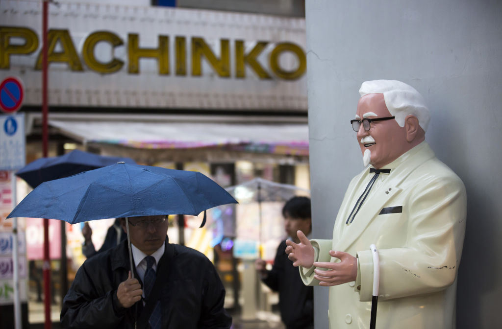 A pedestrian holding an umbrella walks near a statue of Colonel Harland Sanders, the founder of Kentucky Fried Chicken (KFC), outside a Kentucky Fried Chicken Japan Ltd. restaurant in the Akihabara district of Tokyo, Japan, on Thursday, Feb. 9, 2017.