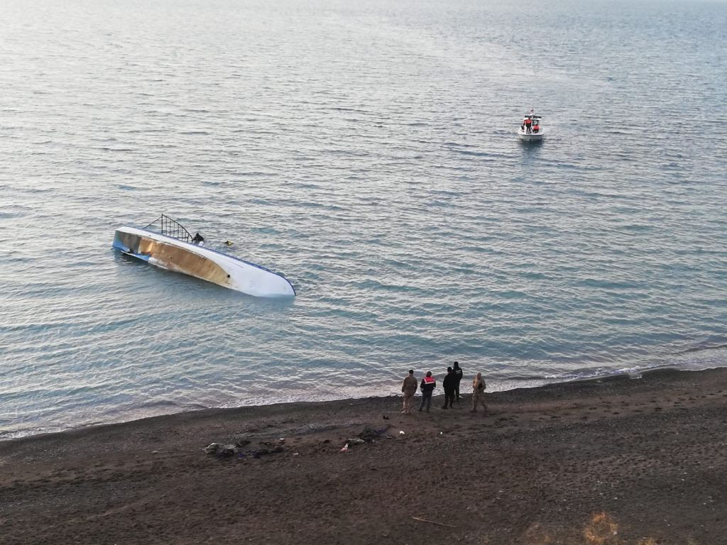 Officials wait at the shore of Lake Van after a boat carrying migrants sank on Dec. 26, 2019.