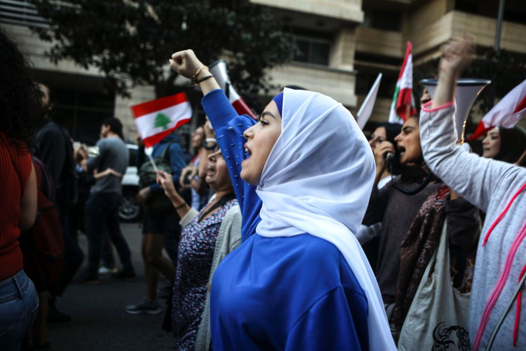 Lebanese anti-government protesters shout slogans as they march on the former demarcation line separating Beirut on Dec. 1, 2019.