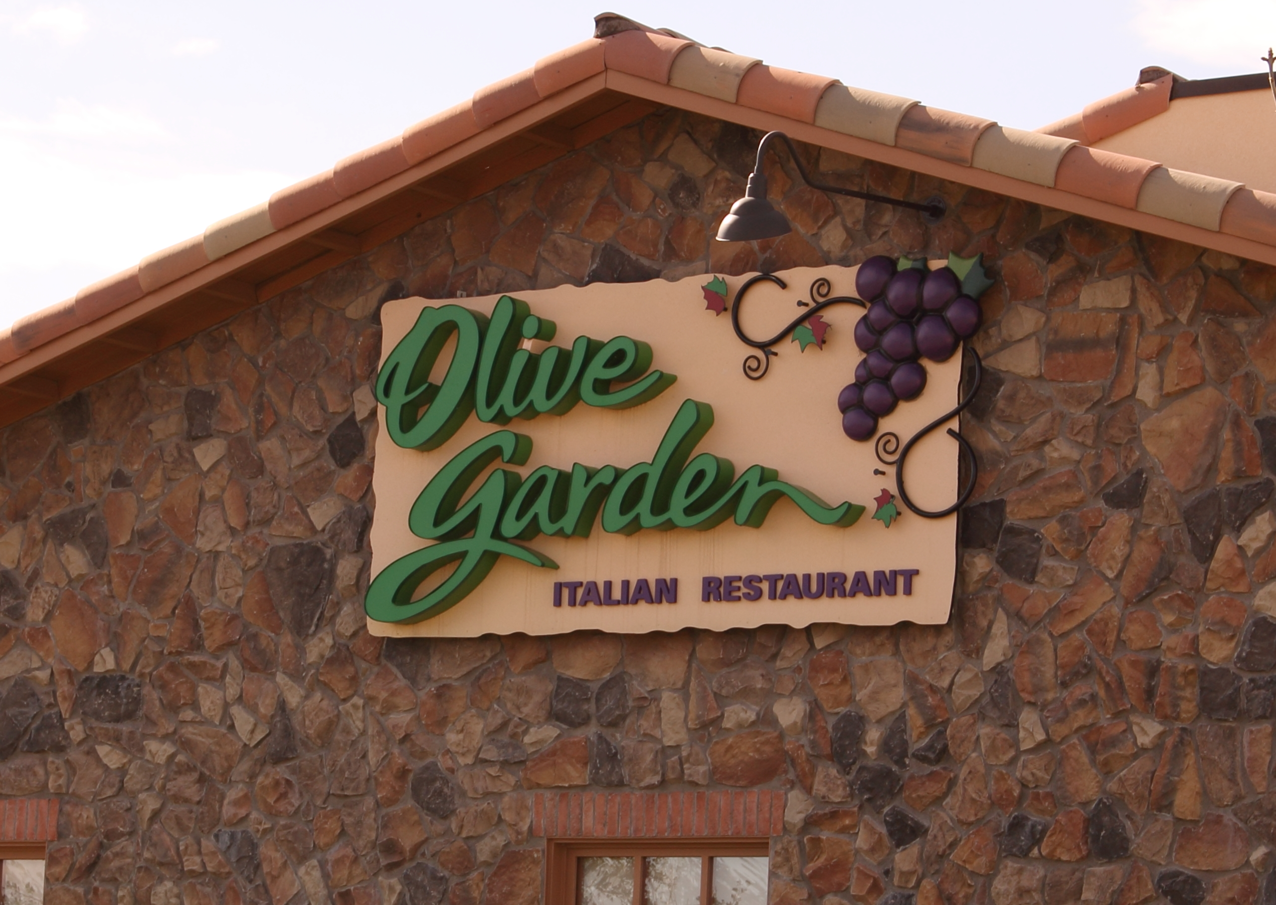 Olive Garden sign on the exterior of a restaurant, the background is stone.