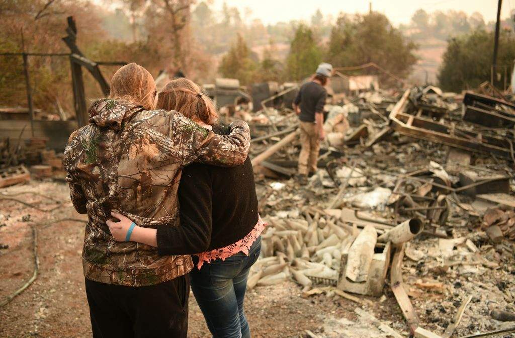 Kimberly Spainhower hugs her daughter Chloe, 13, while her husband Ryan Spainhower (R) searches through the ashes of their burned home in Paradise, California on Nov. 18, 2018.
