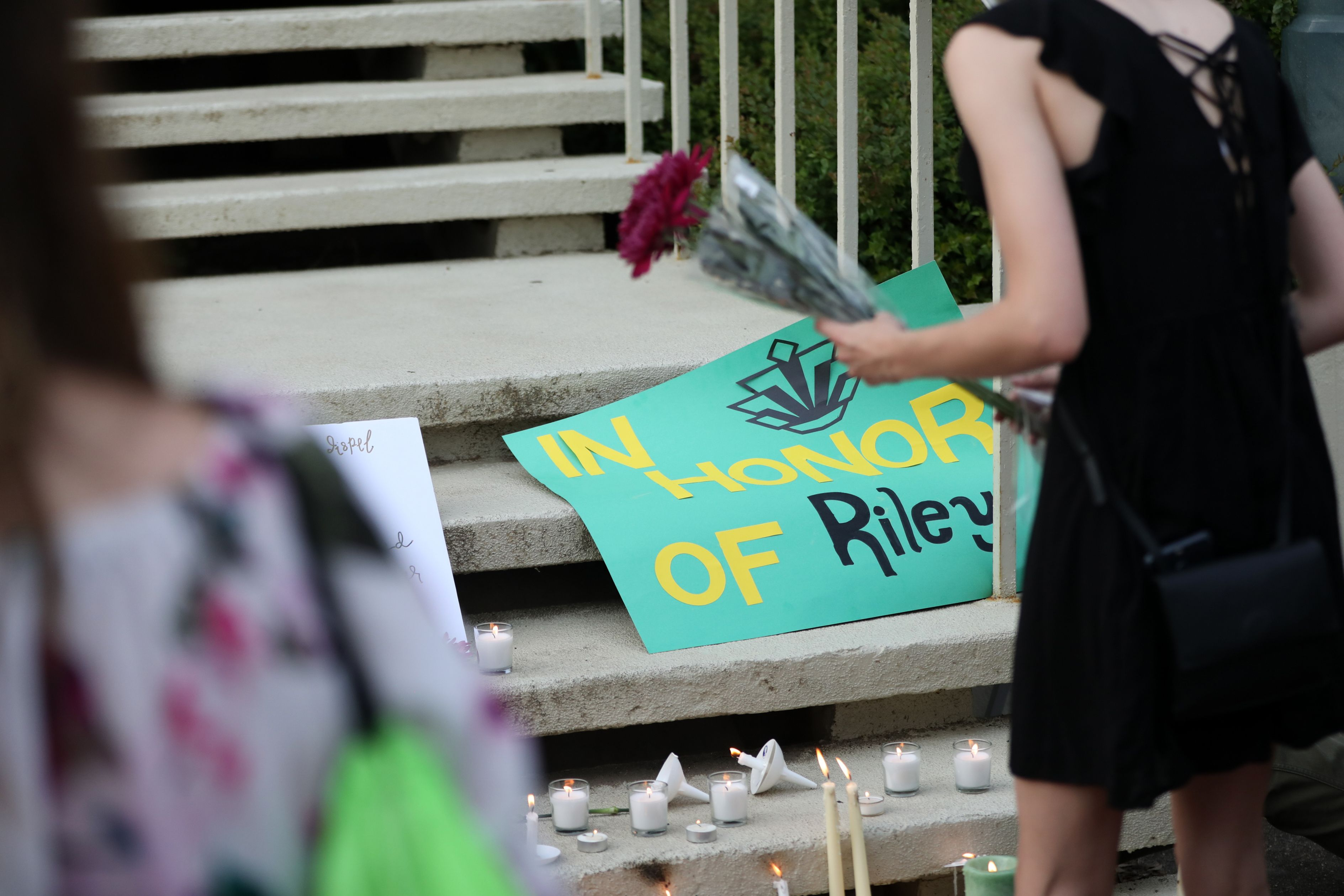 Students lay candles and flowers at the steps of Kennedy Hall to honor the victims of a shooting the day earlier at the University of North Carolina Charlotte, in Charlotte, North Carolina on May 1, 2019.