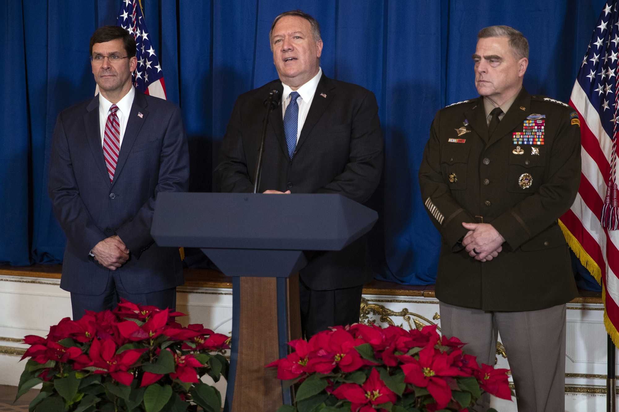 Secretary of Defense Mark Esper, left, and Chairman of the Joint Chiefs of Staff Gen. Mark Milley, right, listen as Secretary of State Mike Pompeo delivers a statement on Iraq and Syria, at President Donald Trump's Mar-a-Lago property, Sunday, Dec. 29, 2019, in Palm Beach, Fla.
