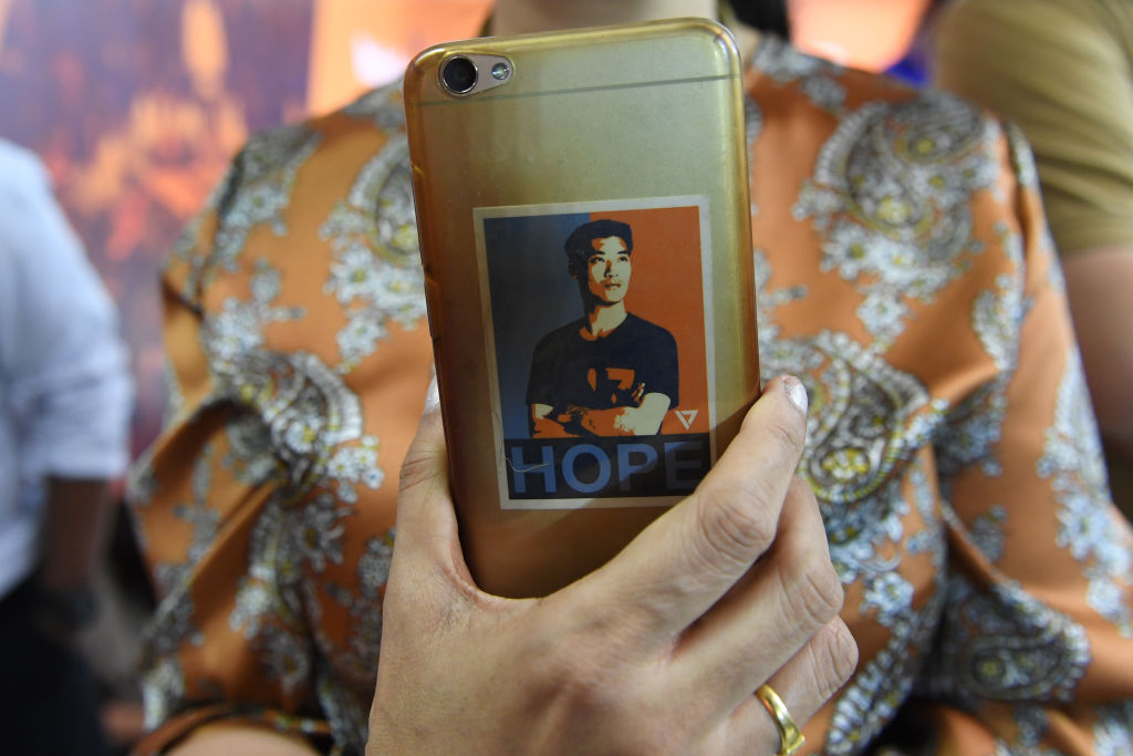 A woman holds a mobile phone decorated with a sticker featuring an image of Future Forward Party leader Thanathorn Juangroongruangkit during the party's press conference in Bangkok on March 25, 2019 after Thailand's general election.