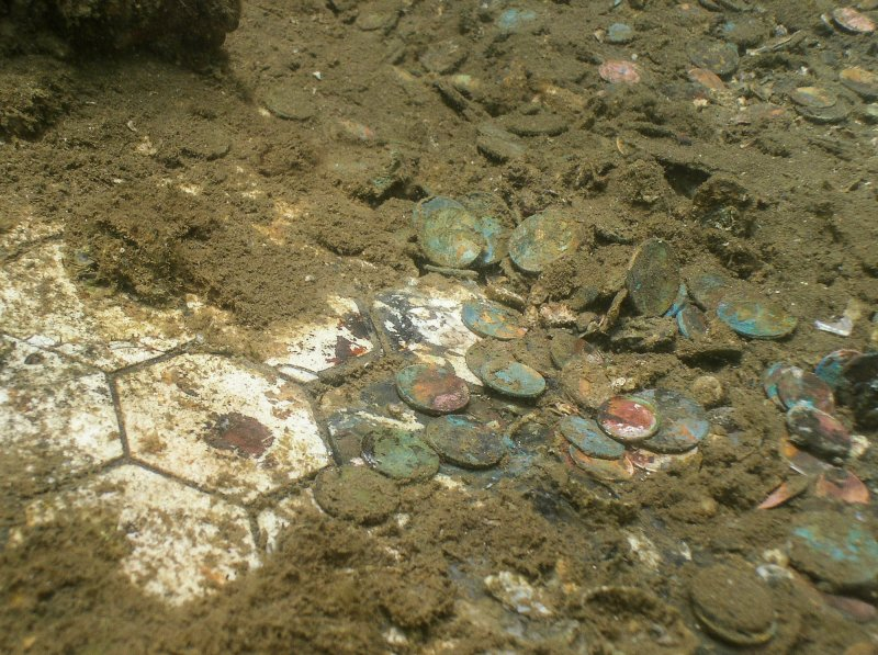 Coins from many nations rest on the white galley floor tiles directly beneath the U.S.S. Arizona's memorial.