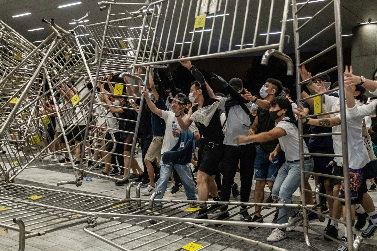 A band of youths in Hong Kong are framed by a puzzle wall of steel barricades during a protest on June 10 against Carrie Lam's proposal to allow extraditions to mainland China.