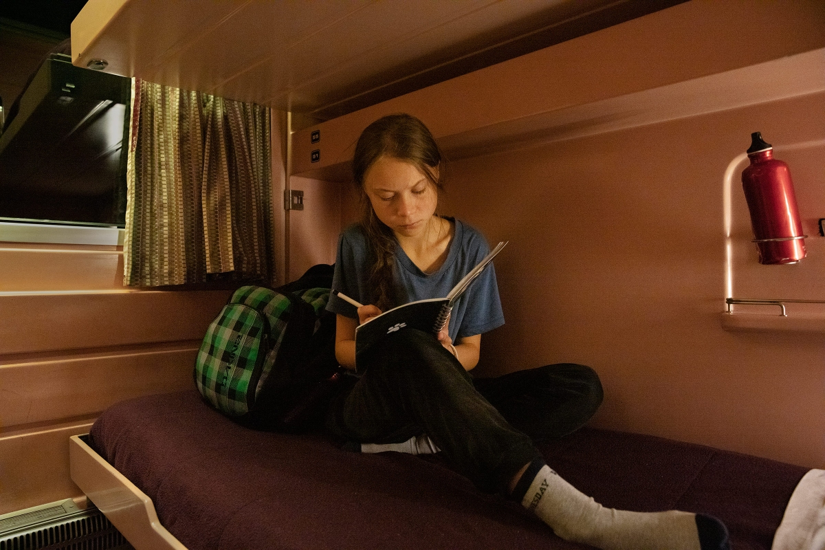 Greta Thunberg writes in her journal on the train as she travels from Lisbon to Madrid for a U.N. climate conference on Dec. 5.