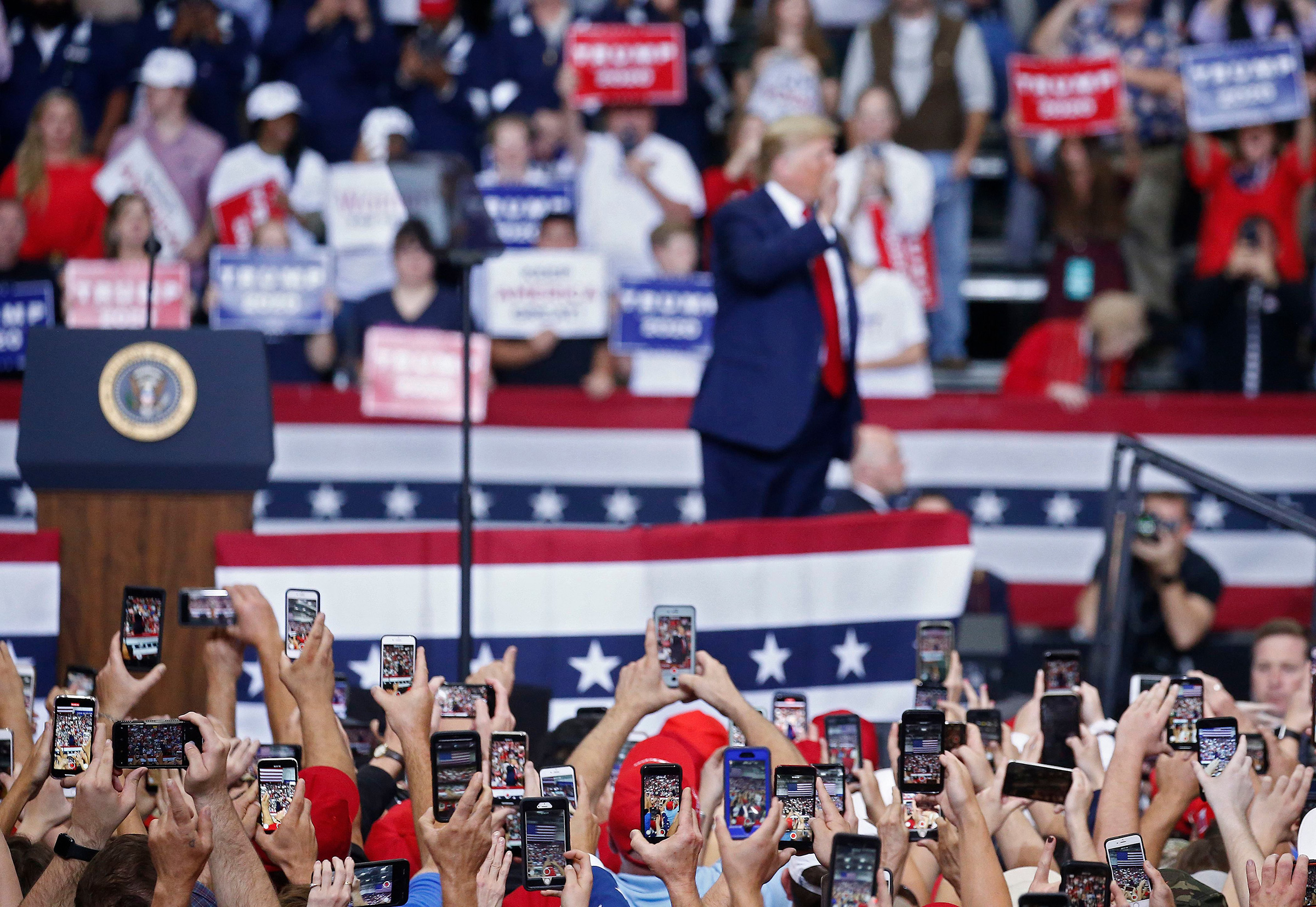 People use their phones to photograph President Donald Trump as he addresses a rally in Monroe,La., on Nov.6