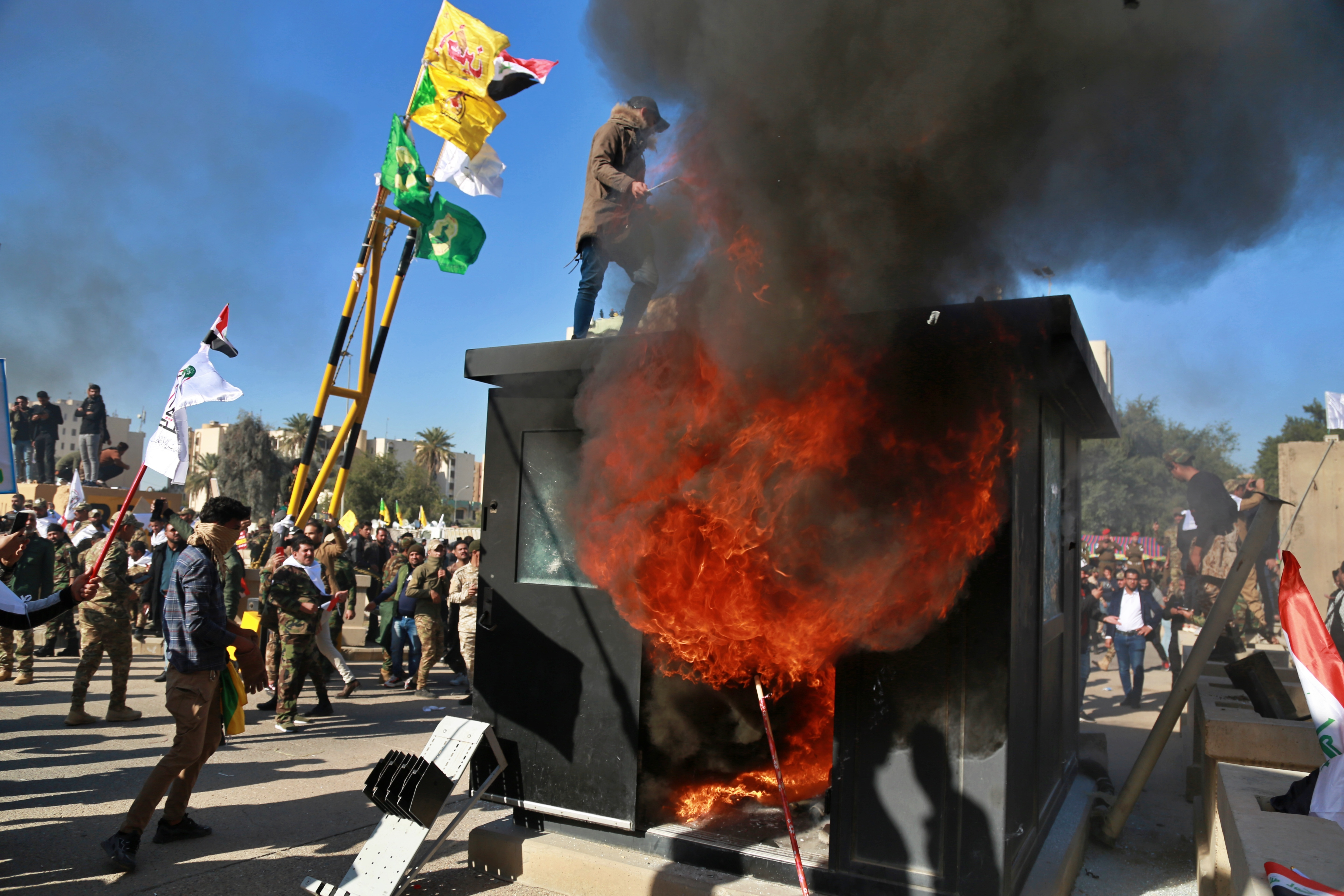 Protesters burn property in front of the U.S. embassy compound, in Baghdad, Iraq, Tuesday, Dec. 31, 2019. Dozens of angry Iraqi Shiite militia supporters broke into the U.S. Embassy compound in Baghdad on Tuesday after smashing a main door and setting fire to a reception area, prompting tear gas and sounds of gunfire.