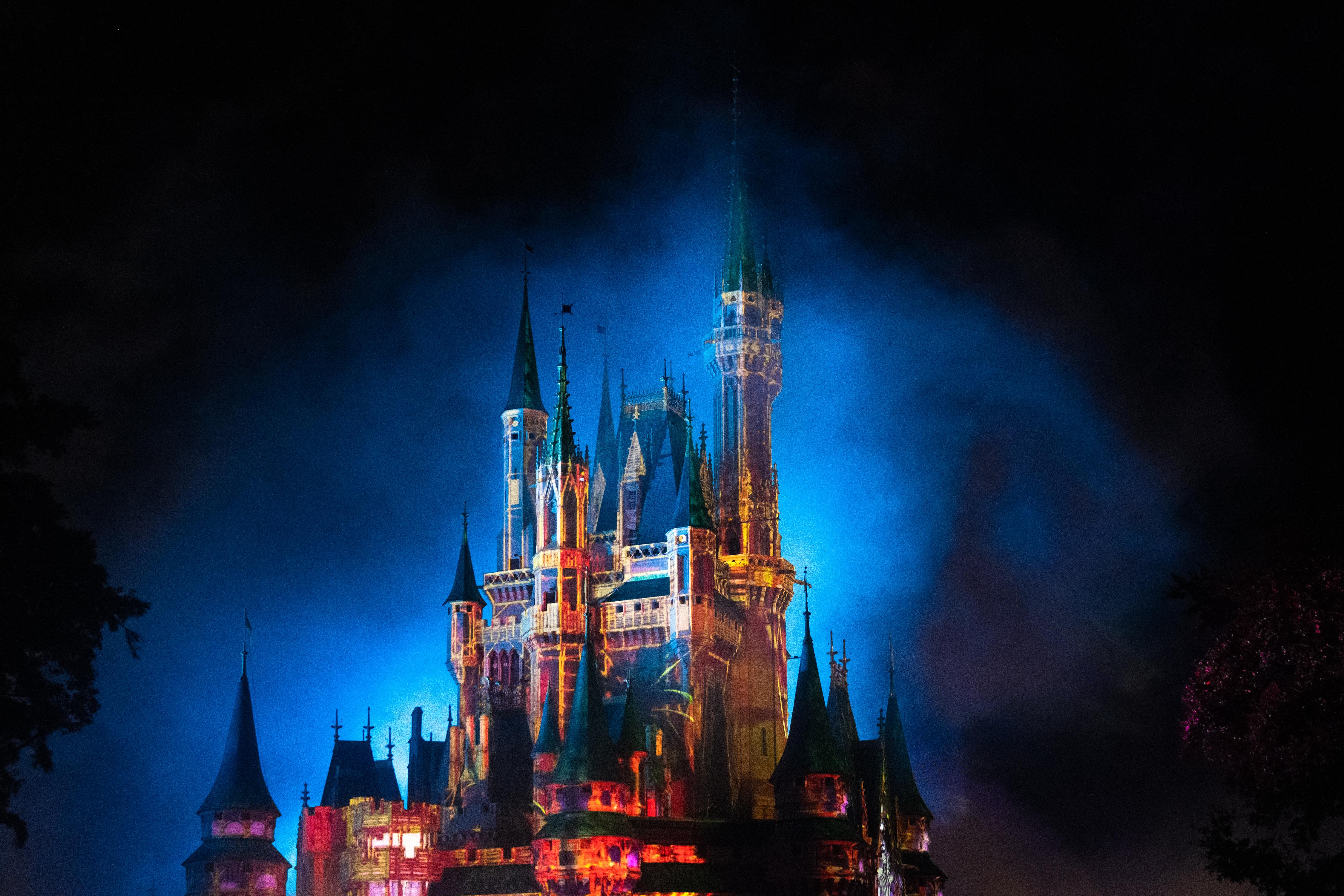 Strobe lights illuminating the Cinderella Castle at Walt Disney's Magic Kingdom at night.