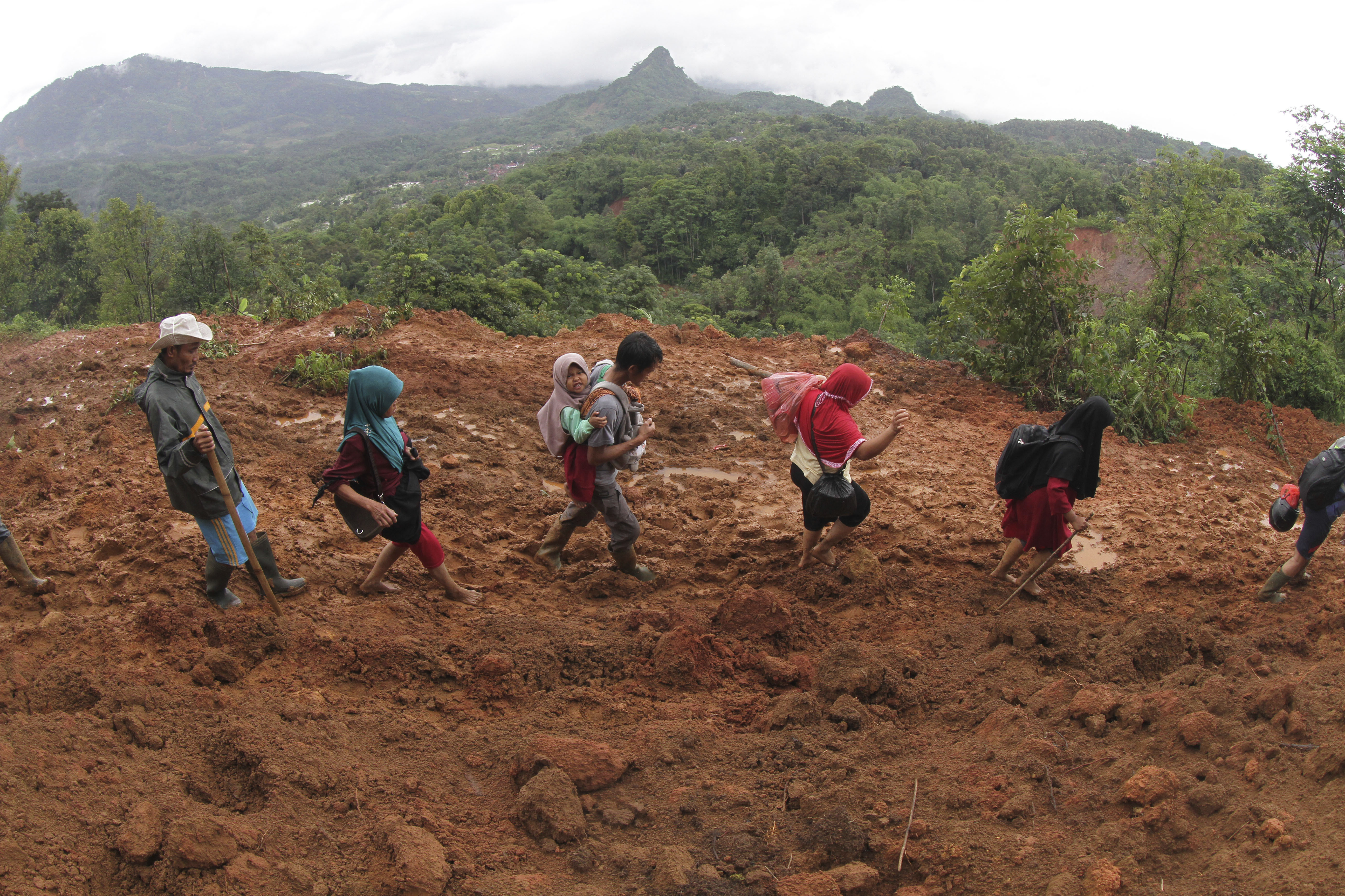 Villagers make their way through an area affected by a landslide in Sukajaya, West Java, Indonesia, on Jan. 5, 2020.