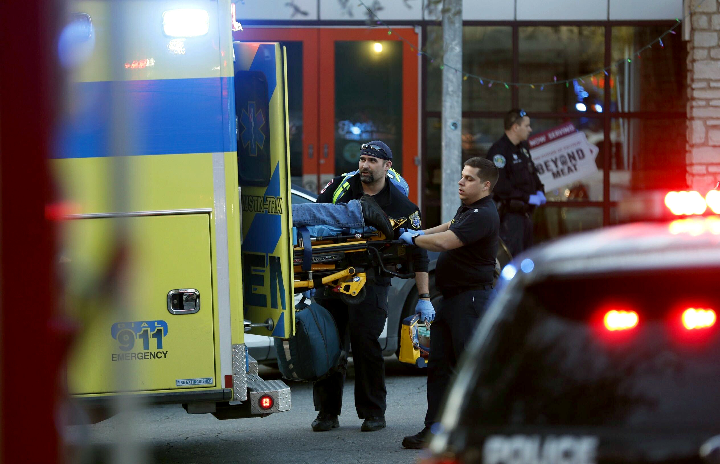 Paramedics transport a stabbing victim as Austin Police secure the area of a shopping complex in Austin, Texas, on Friday, Jan. 3, 2020.