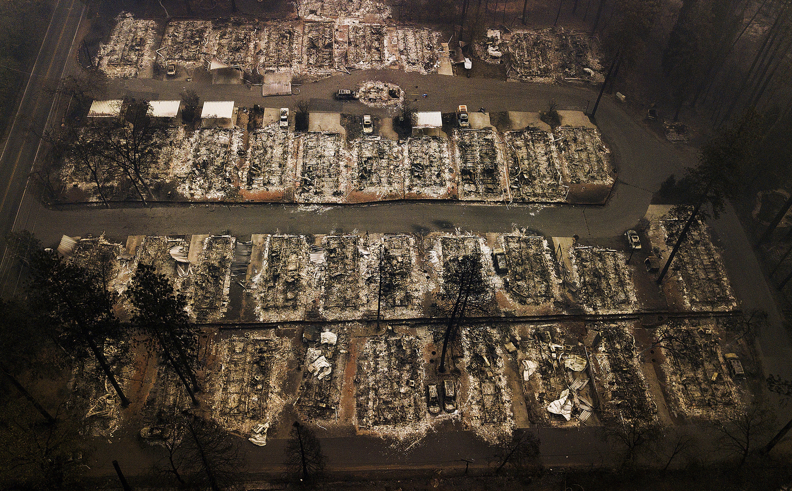 This Nov. 15, 2018, aerial file photo shows the remains of residences leveled by the Camp wildfire in Paradise, Calif. People who lost family members, homes and businesses in California wildfires had a Tuesday, Dec. 31, 2019, deadline to seek compensation from the nation's largest utility as part of its bankruptcy case. The deadline involved claims to receive part of the $13.5 billion Pacific Gas & Electric will pay for losses from deadly wildfires in Northern California in 2017 and 2018.