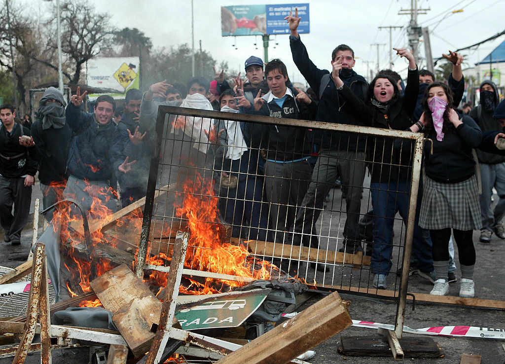 Part of three thousand Chilean students from 21 high schools of the Maipu municipality flash the  v  sign behind a makeshift barricade on 08 August, 2006 in Santiago during the Penguin Revolution.