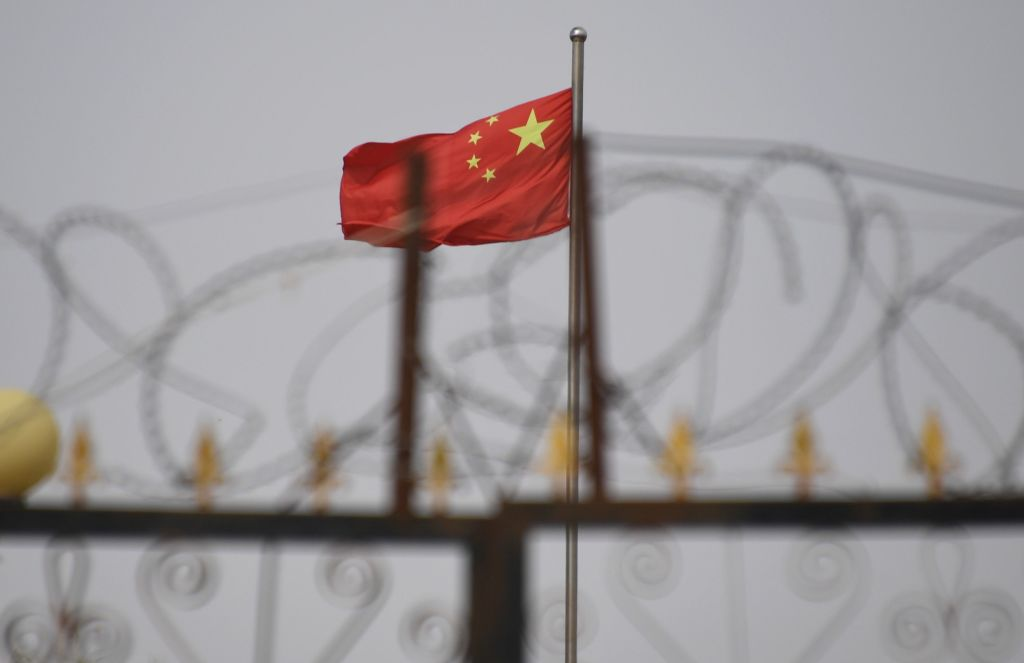 The Chinese flag is seen behind razor wire at a housing compound in Yangisar, south of Kashgar, in China's western Xinjiang region on June 4, 2019.