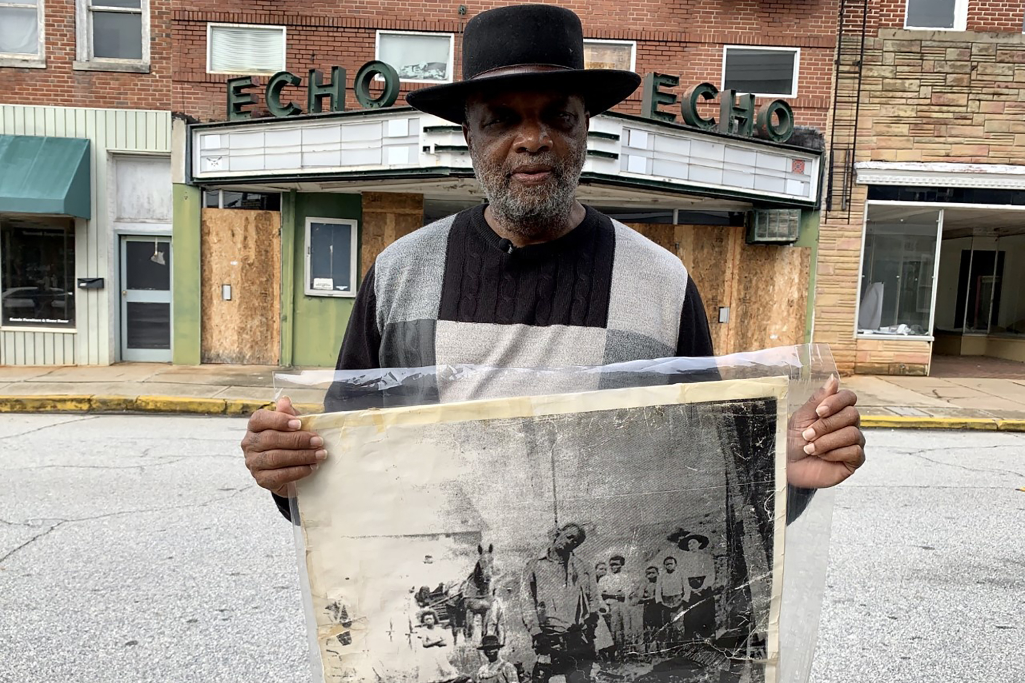In this Jan. 13, 2020 photo, Rev. David Kennedy stands outside the Echo Theater holding a photo of his great uncle's lynching, in Laurens, S.C. Kennedy has fought for civil rights in South Carolina for decades.