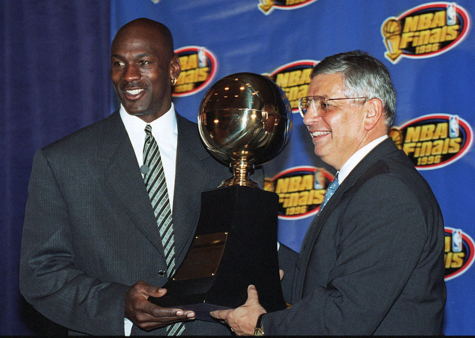 In this June 18, 1996, file photo, Chicago Bulls' Michael Jordan, left, receives the NBA Finals Most Valuable Player trophy from Commissioner David Stern during a ceremony in Chicago. David Stern, who spent 30 years as the NBA's longest-serving commissioner and oversaw its growth into a global power, has died on New Year's Day, Wednesday, Jan. 1, 2020. He was 77.
