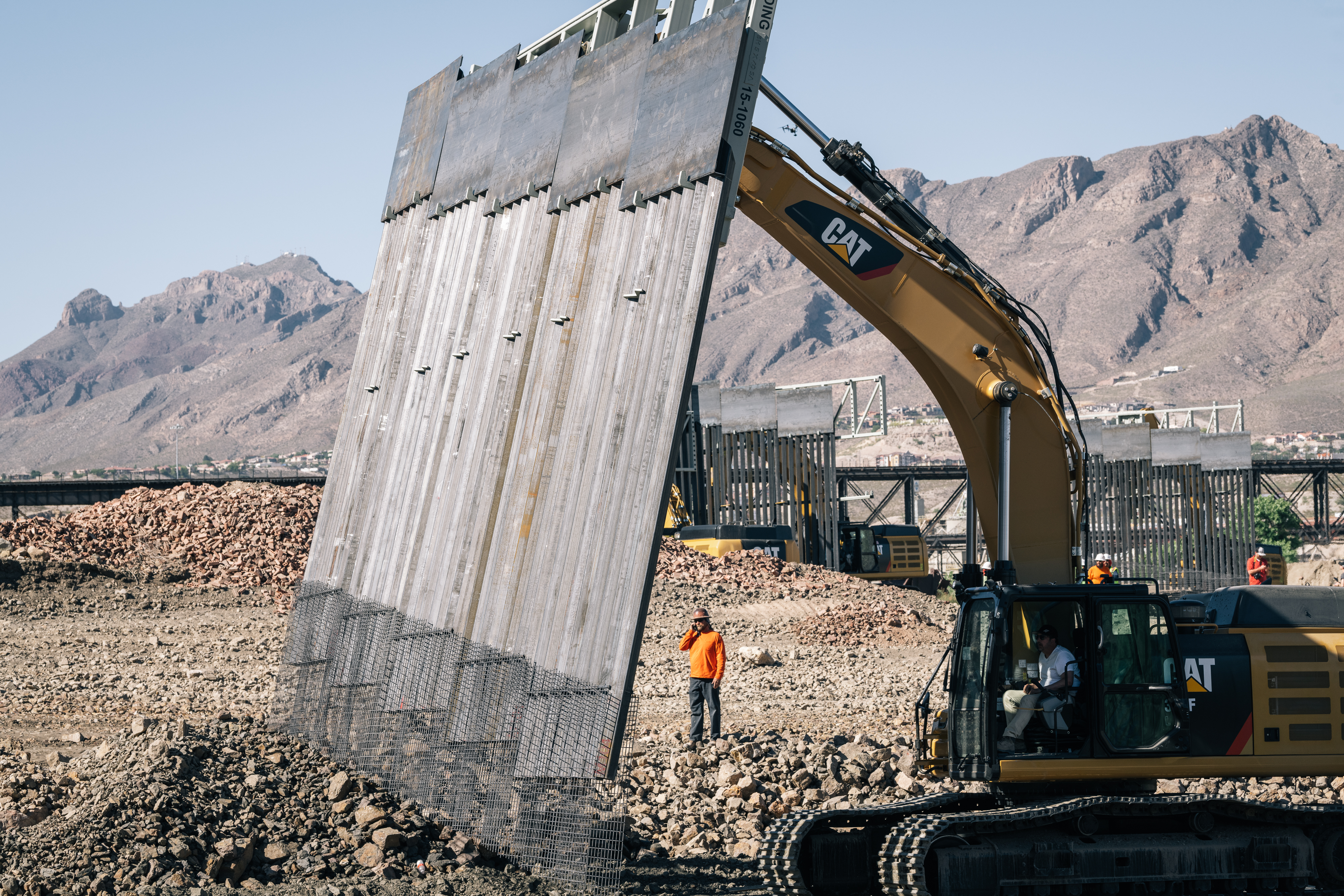Fisher Industries workers drop the first piece  of wall into place on Friday, May 24, 2019 in Sunland Park, New Mexico, on land owned by American Eagle Brick Co, near International Boundary Monument No. 1 where New Mexico, Texas and Mexico come together.