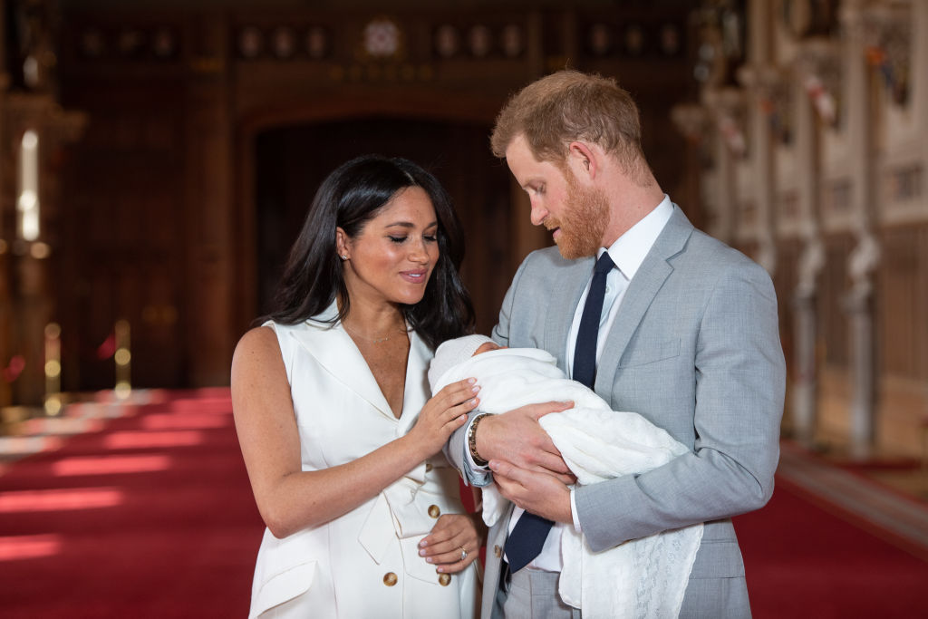 Prince Harry, Duke of Sussex and Meghan, Duchess of Sussex, pose with their newborn son Archie Harrison Mountbatten-Windsor during a photocall in St George's Hall at Windsor Castle on May 8, 2019.