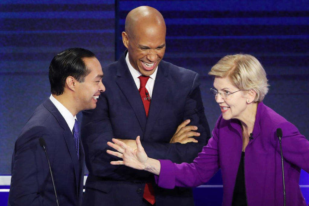 Former housing secretary Julian Castro, Sen. Cory Booker (D-NJ) and Sen. Elizabeth Warren (D-MA) react during the first night of the Democratic presidential debate in Miami, Fla. on June 26, 2019.