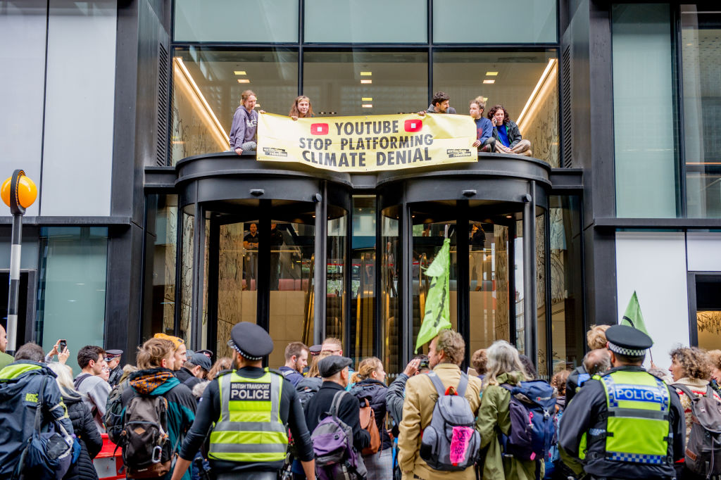 An Extinction Rebellion environmental activist youth group protest on the roof of the entrance to Youtube demanding they stop climate deniers profiting on their platform on October 16, 2019 in London, England.