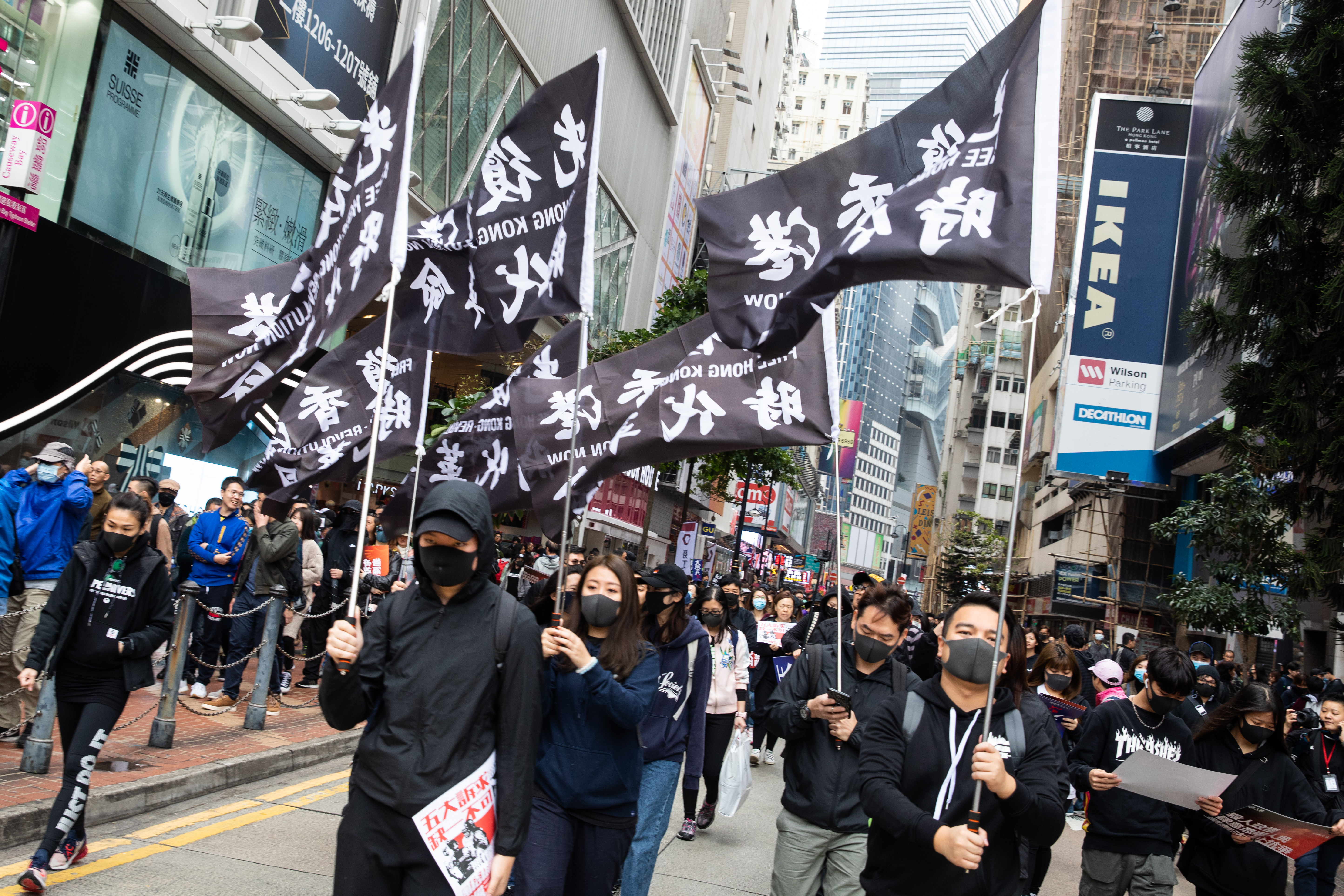 Demonstrators carry flags as they march during a protest in the Causeway Bay district of Hong Kong, China, on Wednesday, Jan. 1, 2020.