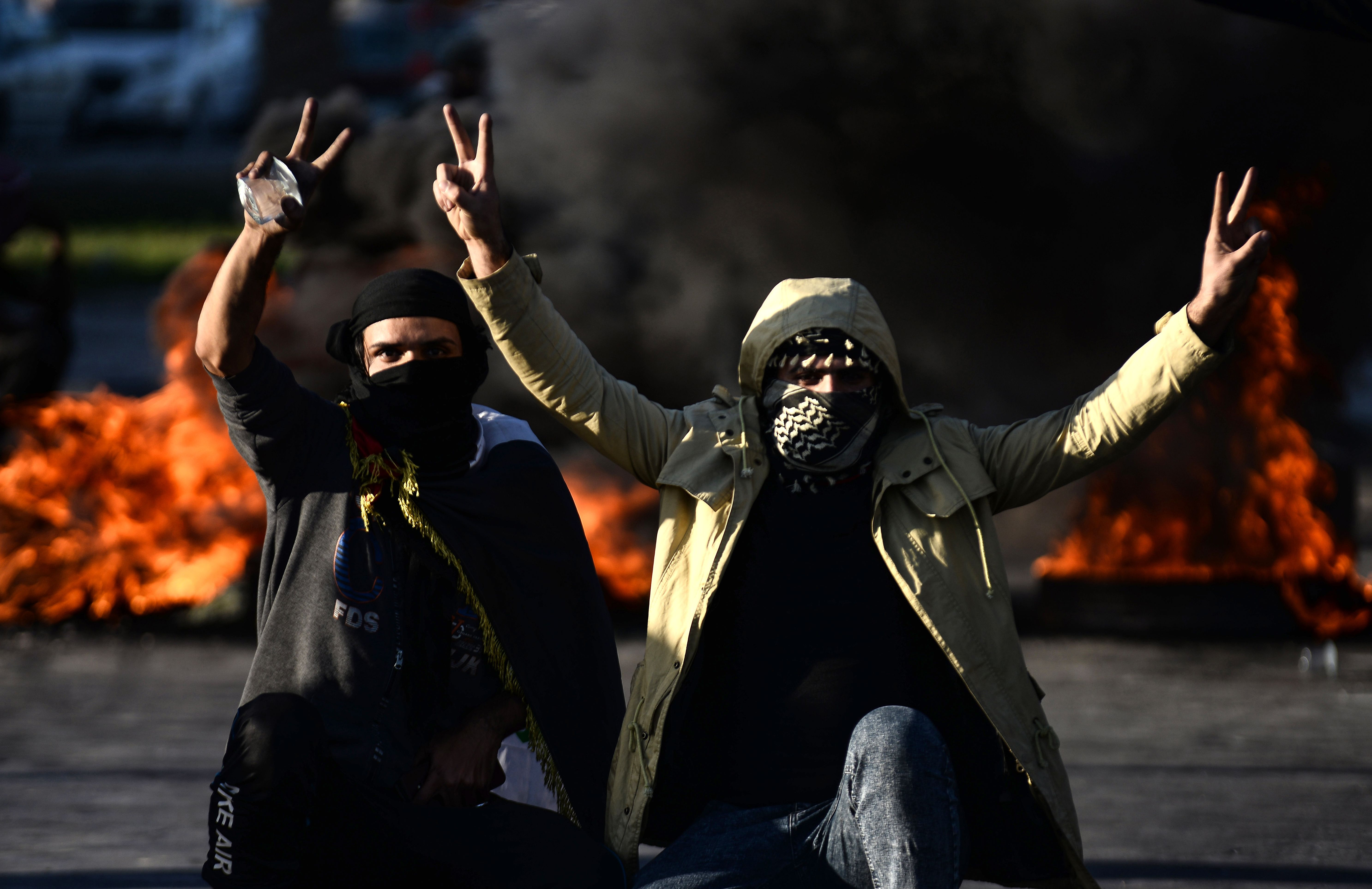 Iraqi demonstrators flash the victory sign next to burning tyres as angry protesters blocked roads in the central shrine city of Najaf, on Jan. 5, 2020