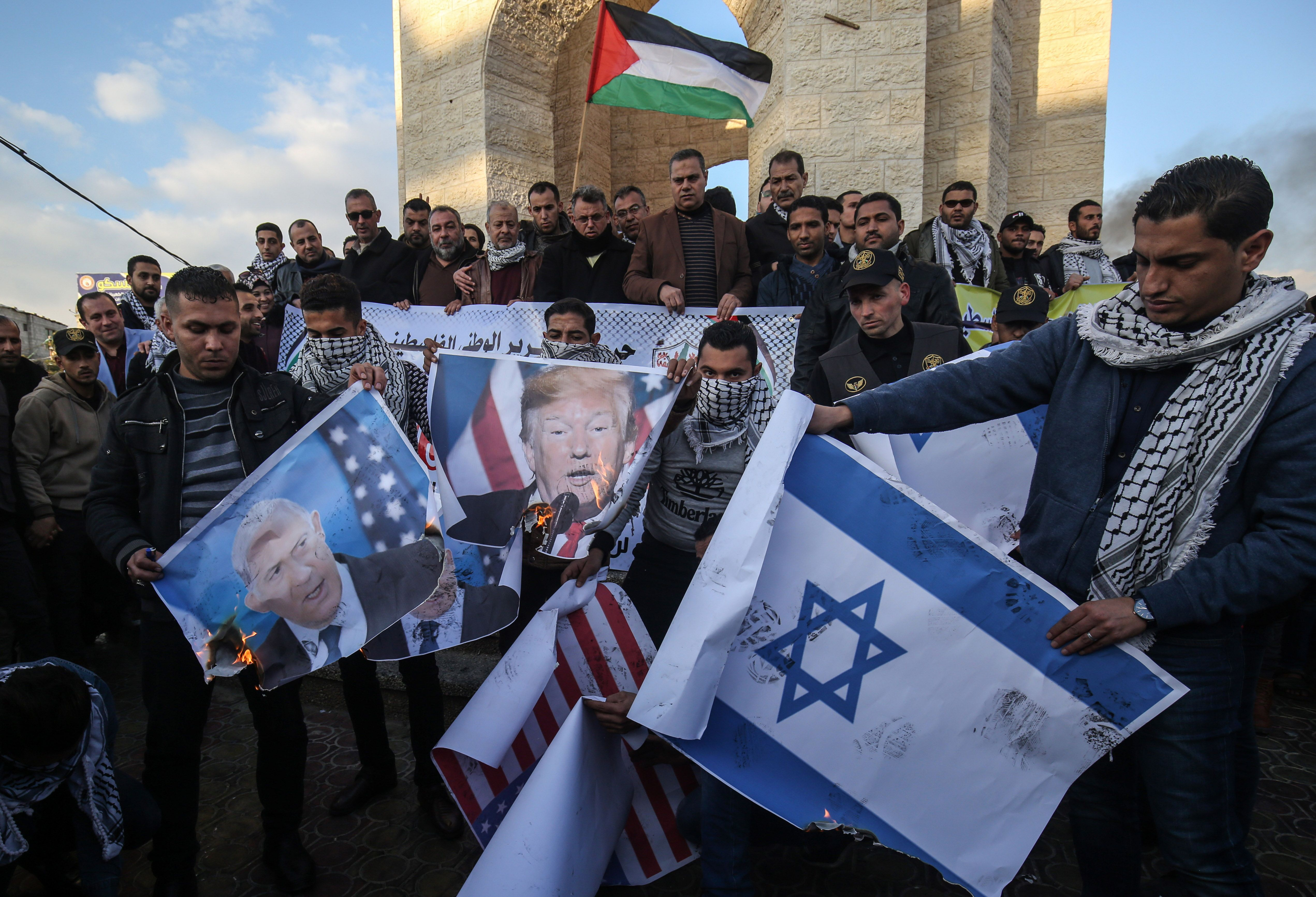Palestinian demonstrators burn images of US President Donald Trump (C) as they protest against a US brokered Middle East peace plan, in Rafah in the southern Gaza Strip, on January 29, 2020.