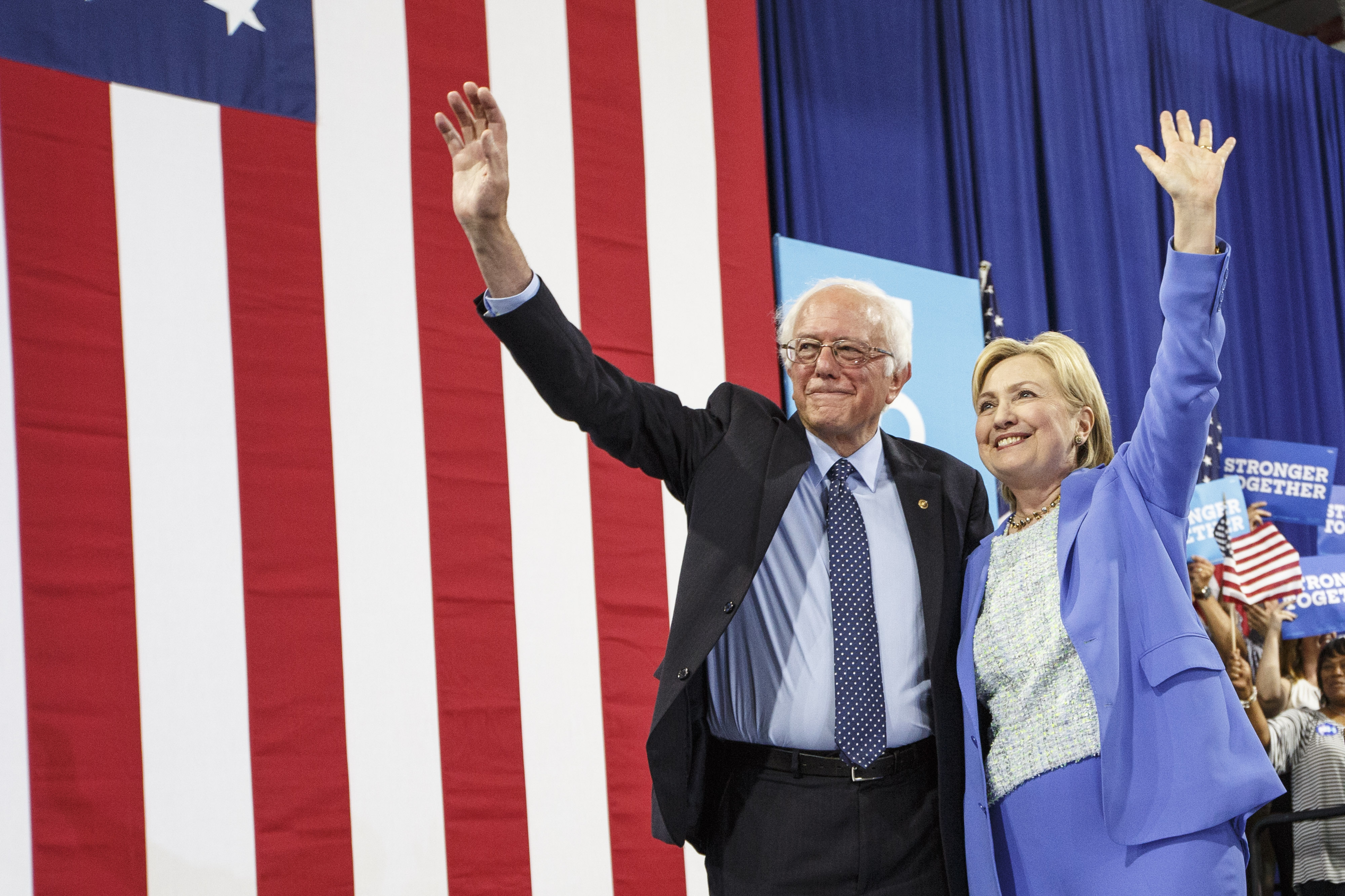 Presidential candidate Hillary Clinton and U.S. Senator and former presidential candidate Bernie Sanders wave from the stage during a campaign event in Portsmouth, N.H., July 12, 2016, in which Sanders endorsed Clinton.