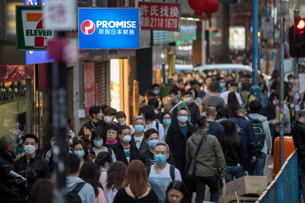 People wearing masks walk on a street in Kwun Tong district of Hong Kong on Jan. 23, 2020.