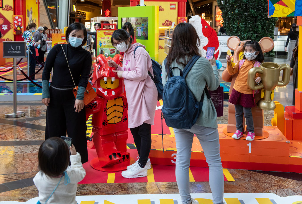 People cover their faces with sanitary masks as they take photos at a shopping mall after the first cases of coronavirus from Wuhan, China were confirmed in Hong Kong.