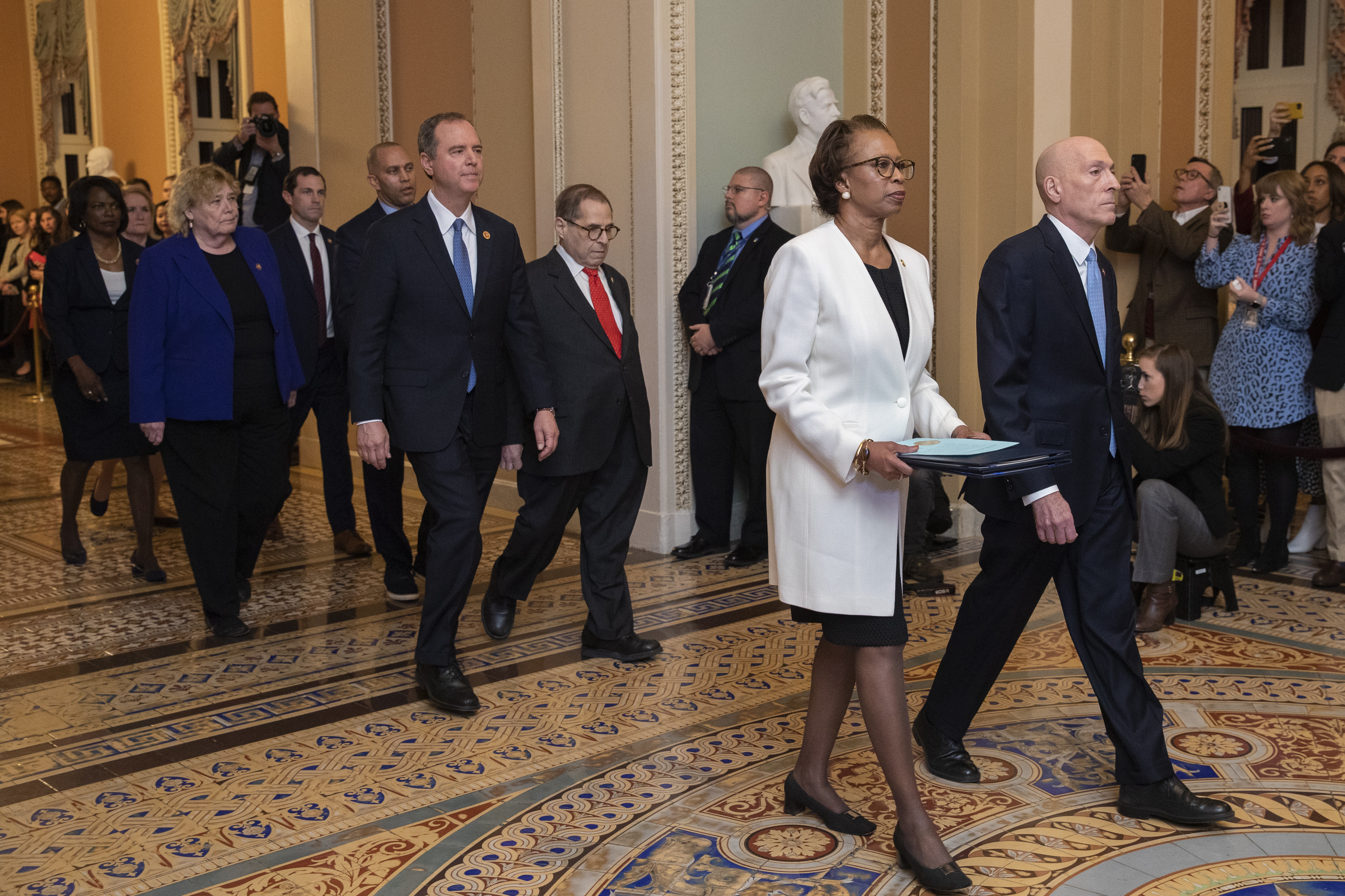House Sergeant at Arms Paul Irving and Clerk of the House Cheryl Johnson carry the articles of impeachment against President Donald Trump to Secretary of the Senate Julie Adams on Capitol Hill in Washington, Wednesday, Jan. 15, 2020. Following are impeachment managers, House Judiciary Committee Chairman, Rep. Jerrold Nadler, D-N.Y., House Intelligence Committee Chairman Adam Schiff, D-Calif., Rep. Hakeem Jeffries, D-N.Y., Rep. Sylvia Garcia, D-Texas, Rep. Val Demings, D-Fla., Rep. Zoe Lofgren, D-Calif., and Rep. Jason Crow, D-Colo. (AP Photo/Manuel Balce Ceneta) , Wednesday, Jan. 15, 2020.