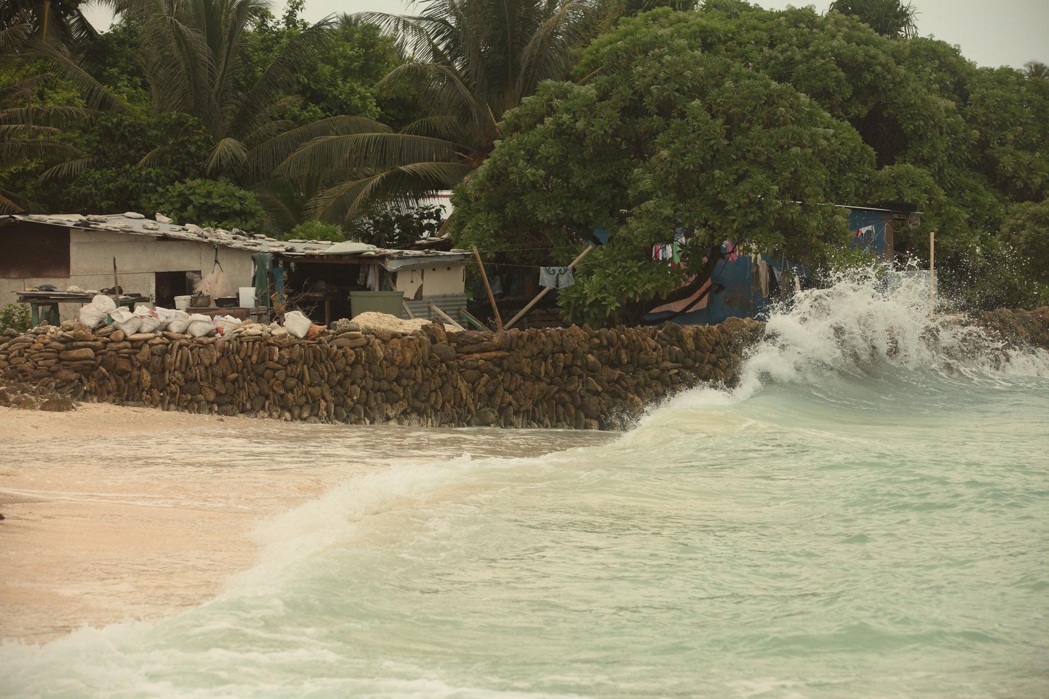 Waves hit a makeshift wall, protecting a coastal house from rising sea levels on Tarawa island, Kiribati.