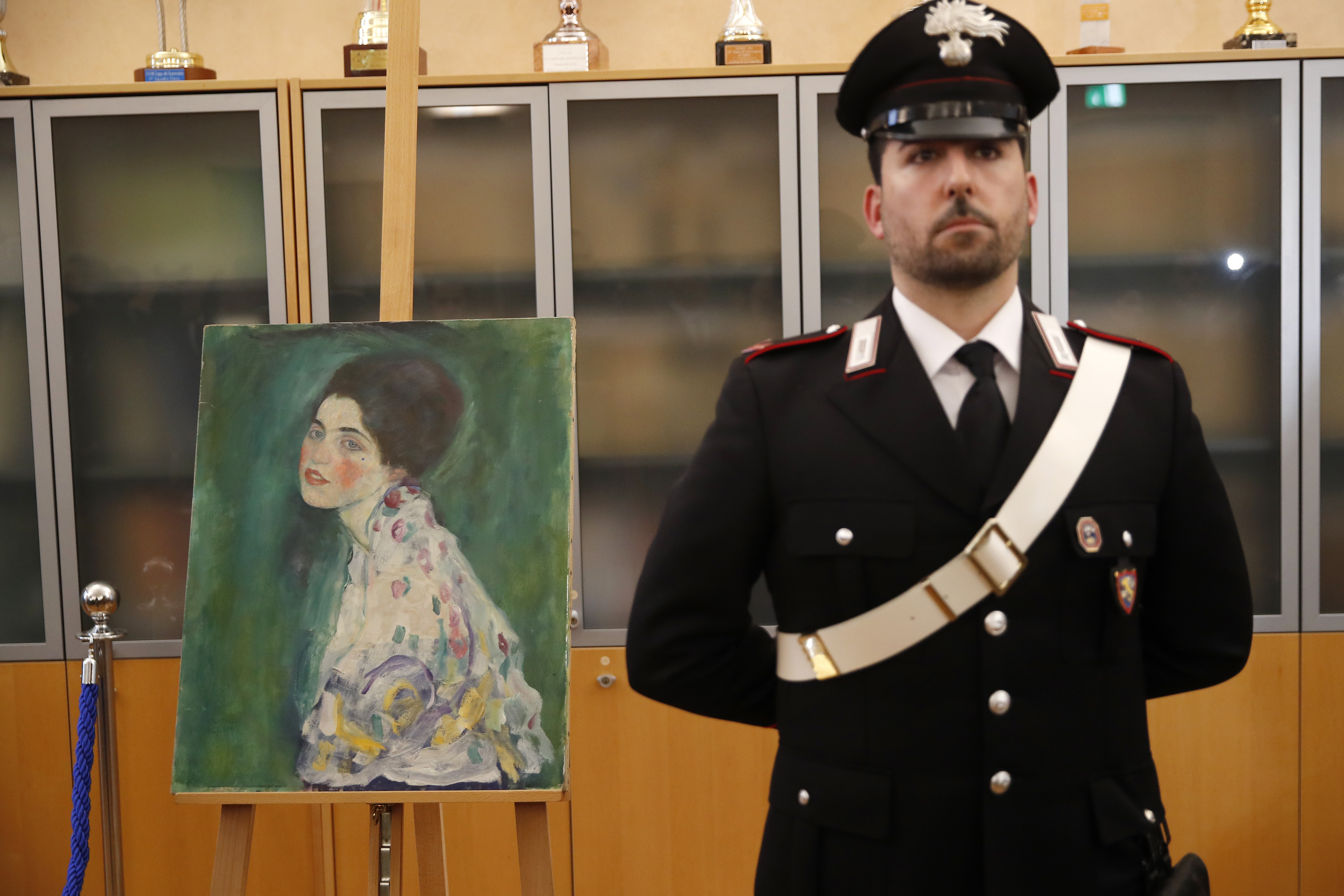An Italian Carabiniere, paramilitary police officer, stands near a painting which was found last December near an art gallery and believed to be the missing Gustav Klimt's painting 'Portrait of a Lady' during a press conference in Piacenza, Italy, Friday, Jan. 17, 2020.