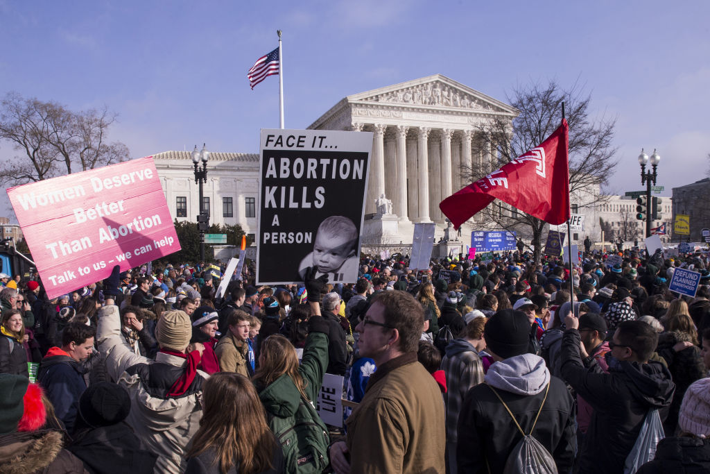 Anti-abortion demonstrators hold signs while marching past the U.S. Supreme Court during the 46th annual March for Life in Washington, D.C.