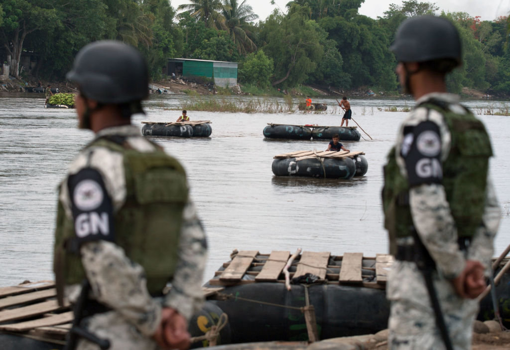 National Guard members stand guard along the banks of the Suchiate river in Ciudad Hidalgo, Chiapas State, Mexico, to prevent illegal crossings across the border river to and from Tecun Uman in Guatemala, on July 3, 2019.