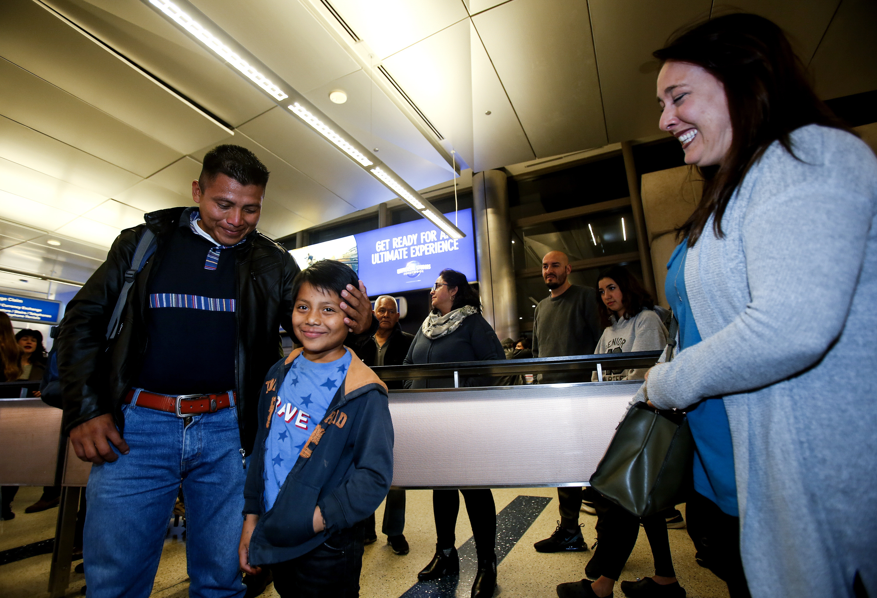 David Xol-Cholom, left, of Guatemala reunites with his son Byron, as Holly Sewell, right, sponsor mom to Bryon, looks on at Los Angeles International Airport after being separated about one and half year ago during the Trump administration's wide-scale separation of immigrant families, Wednesday, Jan. 22, 2020, in Los Angeles.