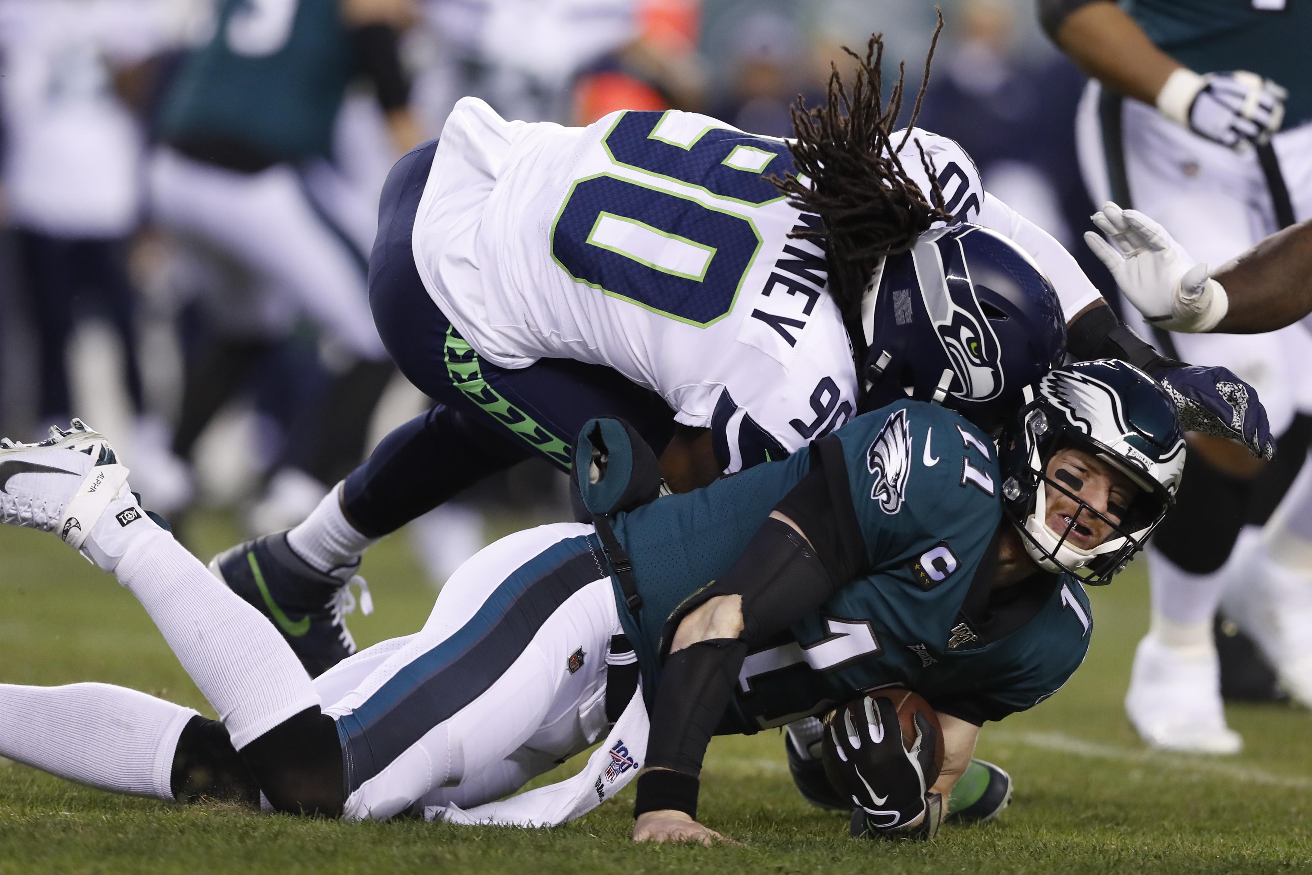 Seattle Seahawks' Jadeveon Clowney (90) hits Philadelphia Eagles' Carson Wentz (11) during the first half of an NFL wild-card playoff football game in Philadelphia on Jan. 5, 2020.